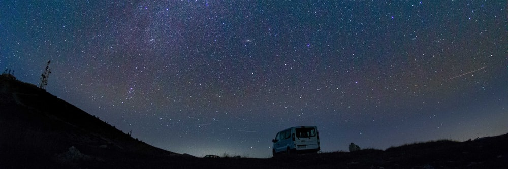 van parked on terrain under starry sky