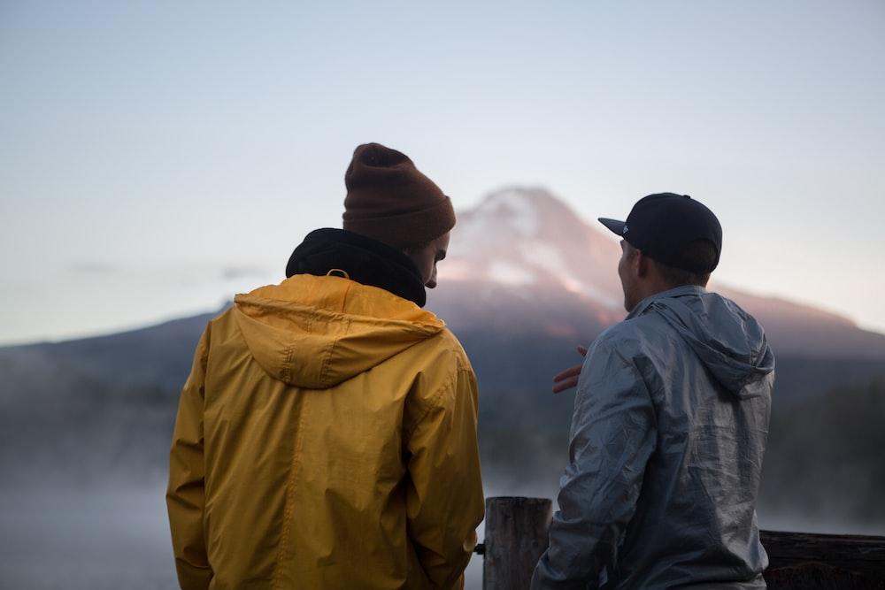 man standing beside man during daytime