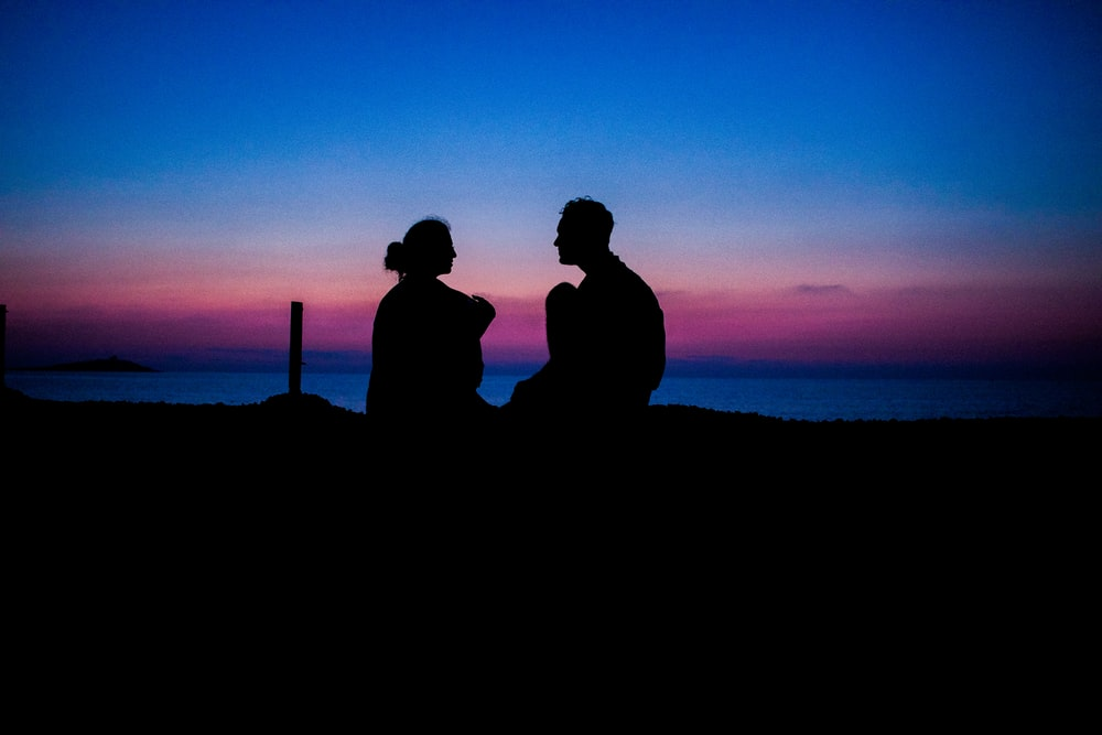 silhouette of man and woman sitting