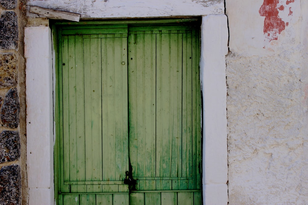 two green wooden doors both closed