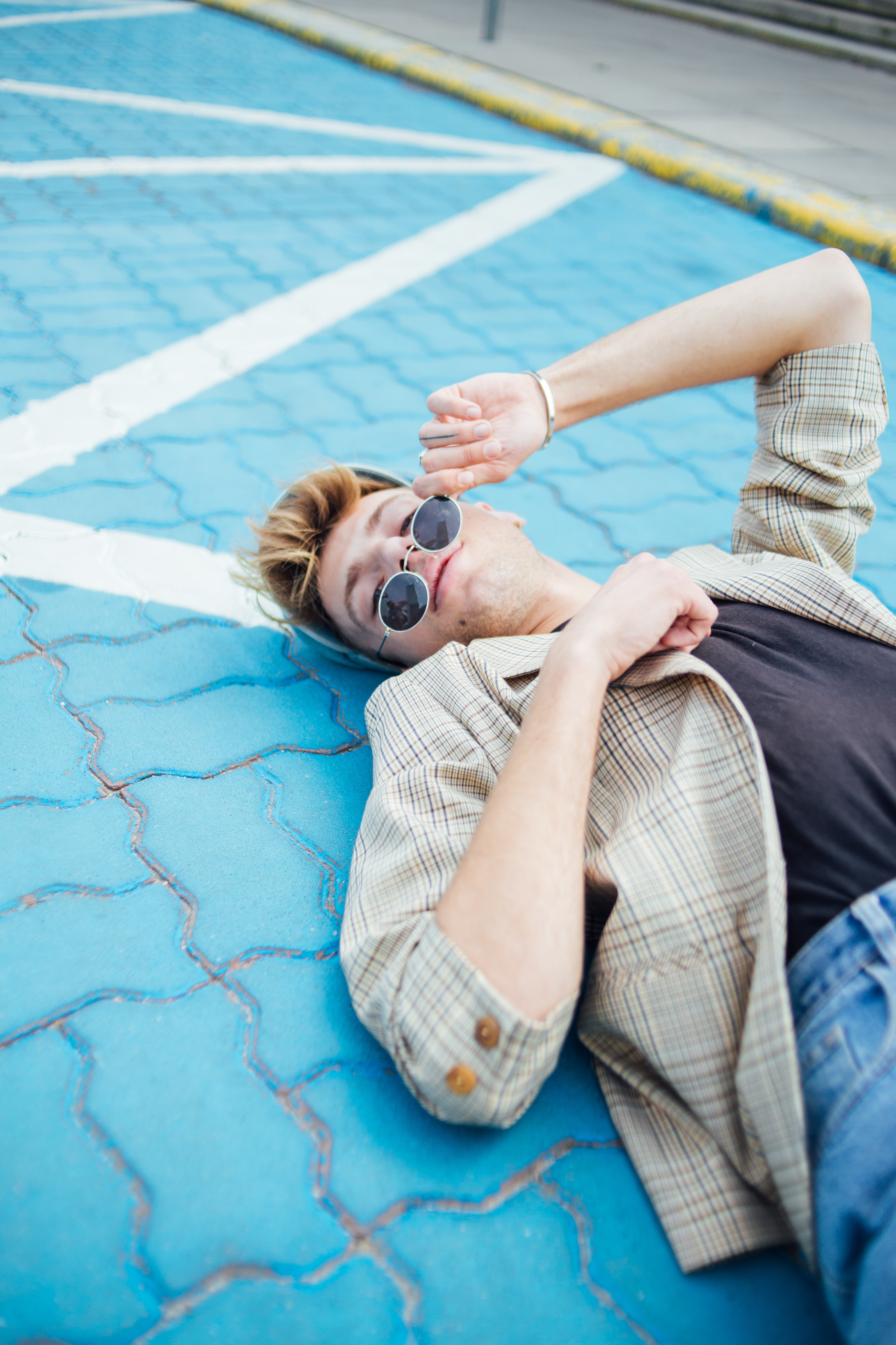 man lying on blue pavement