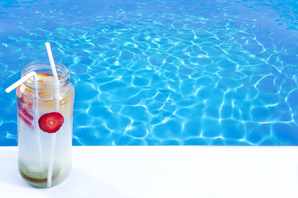 clear glass jar in front of pool