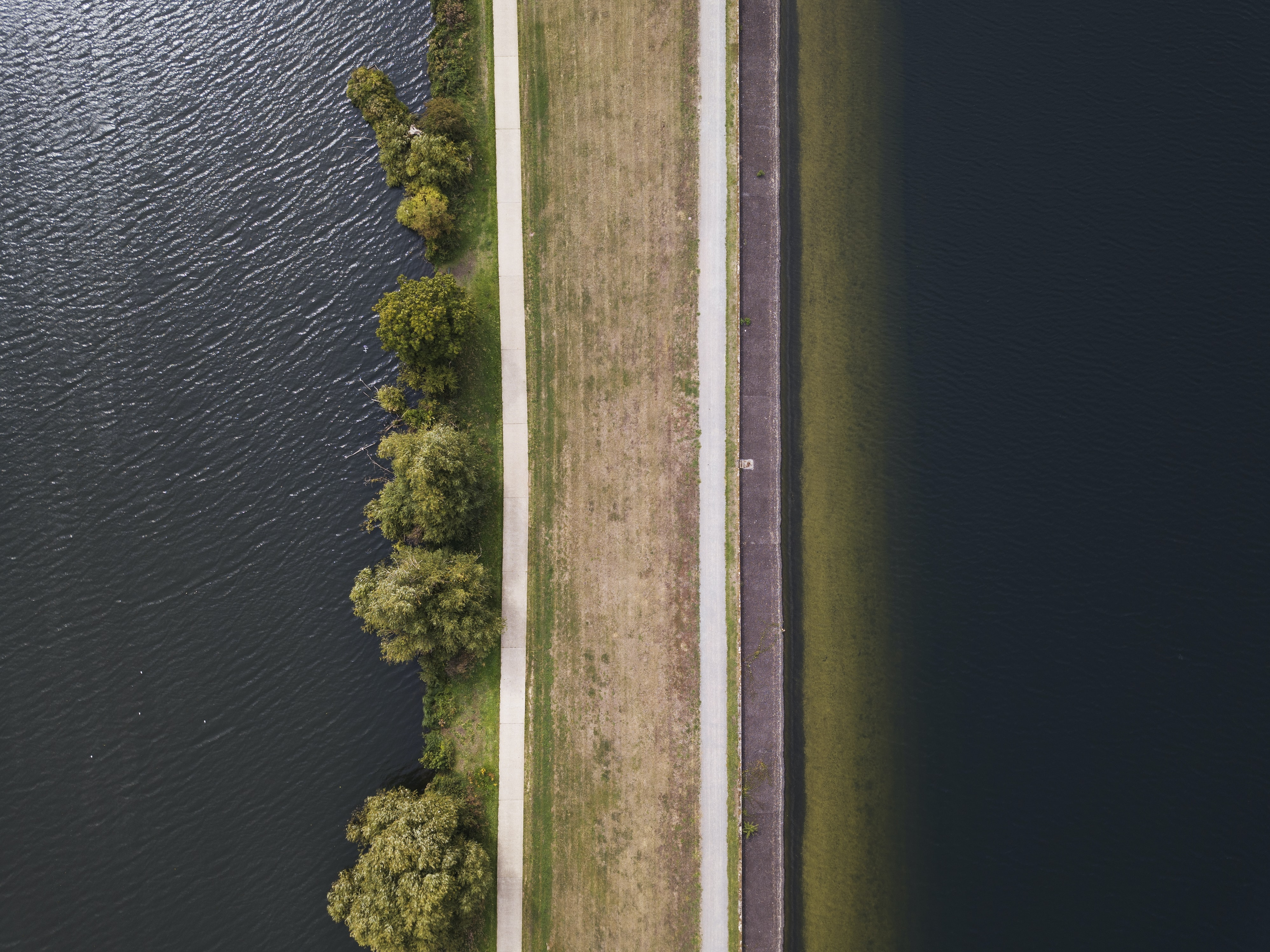 aerial photography of brown road near the body of water at daytime