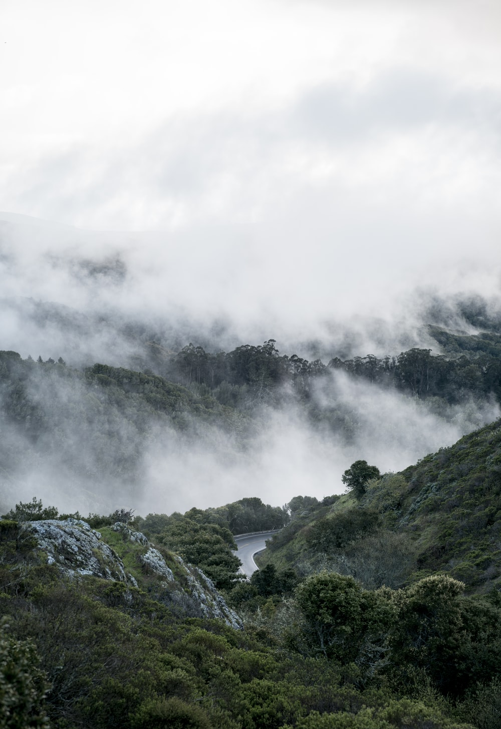 body of water between mountain under foggy sky