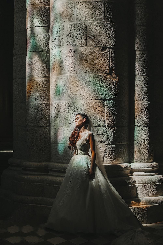 bride standing beside concrete pillar