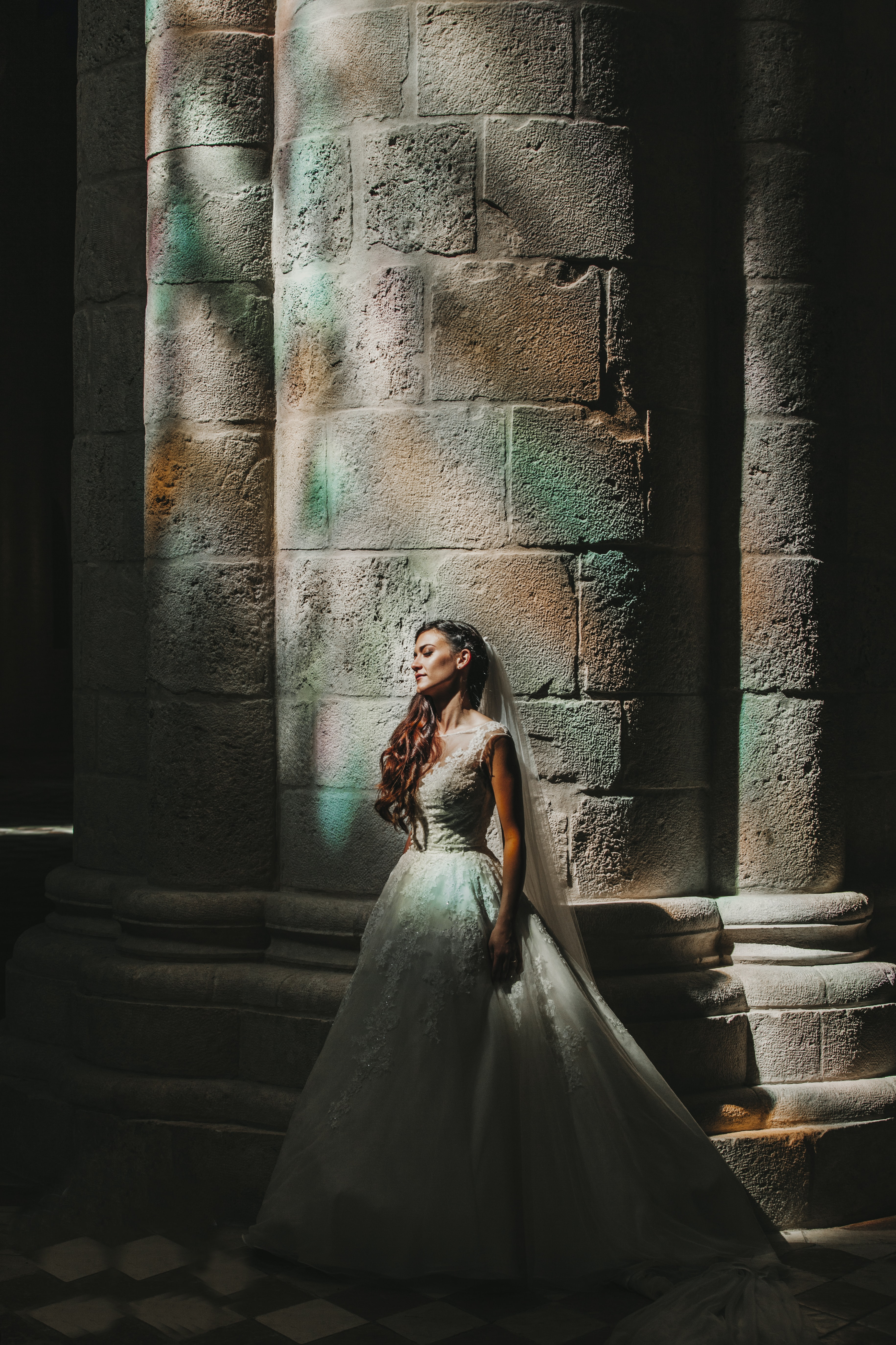 bride standing beside concrete pillar