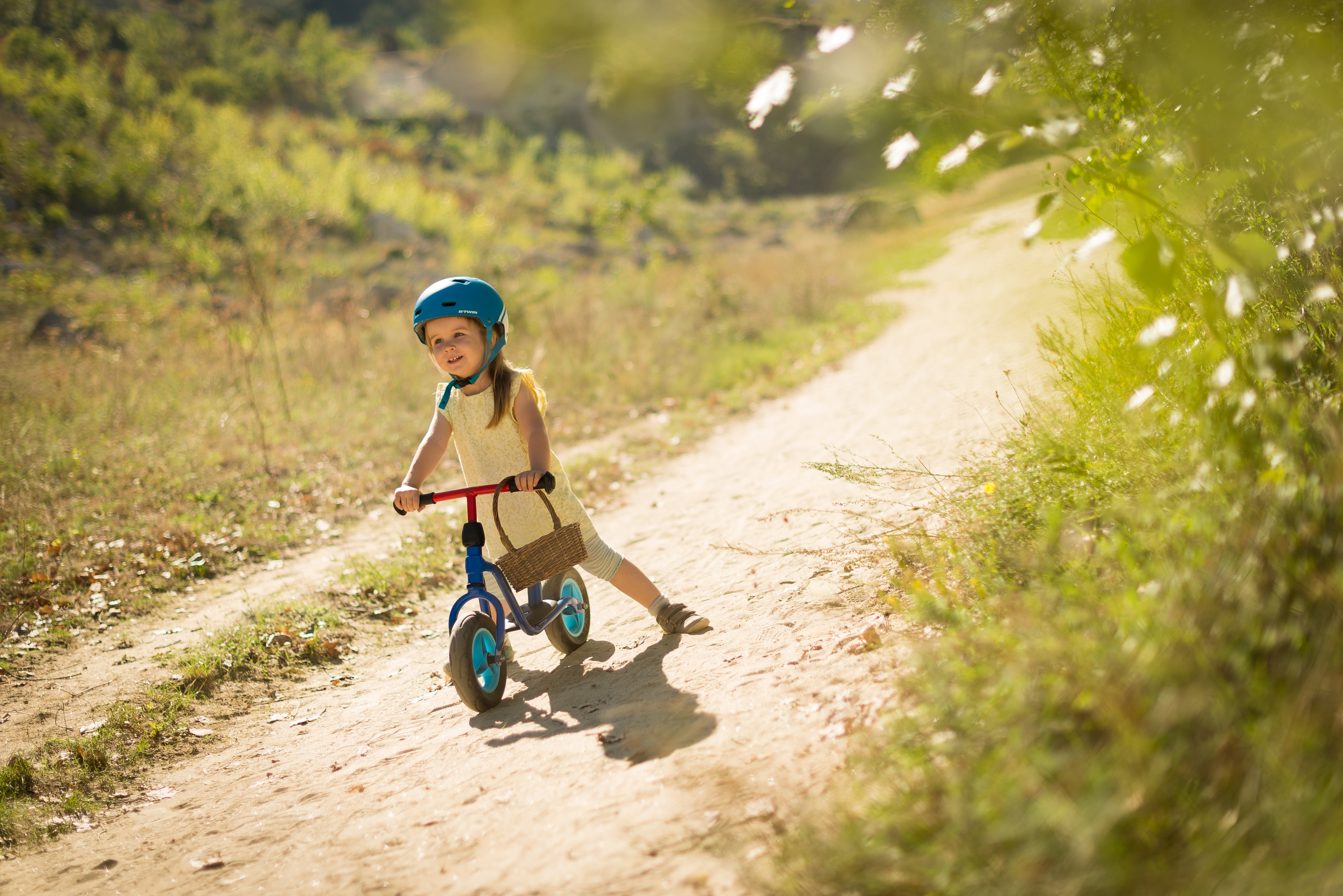 girl riding blue balance bike on pathway