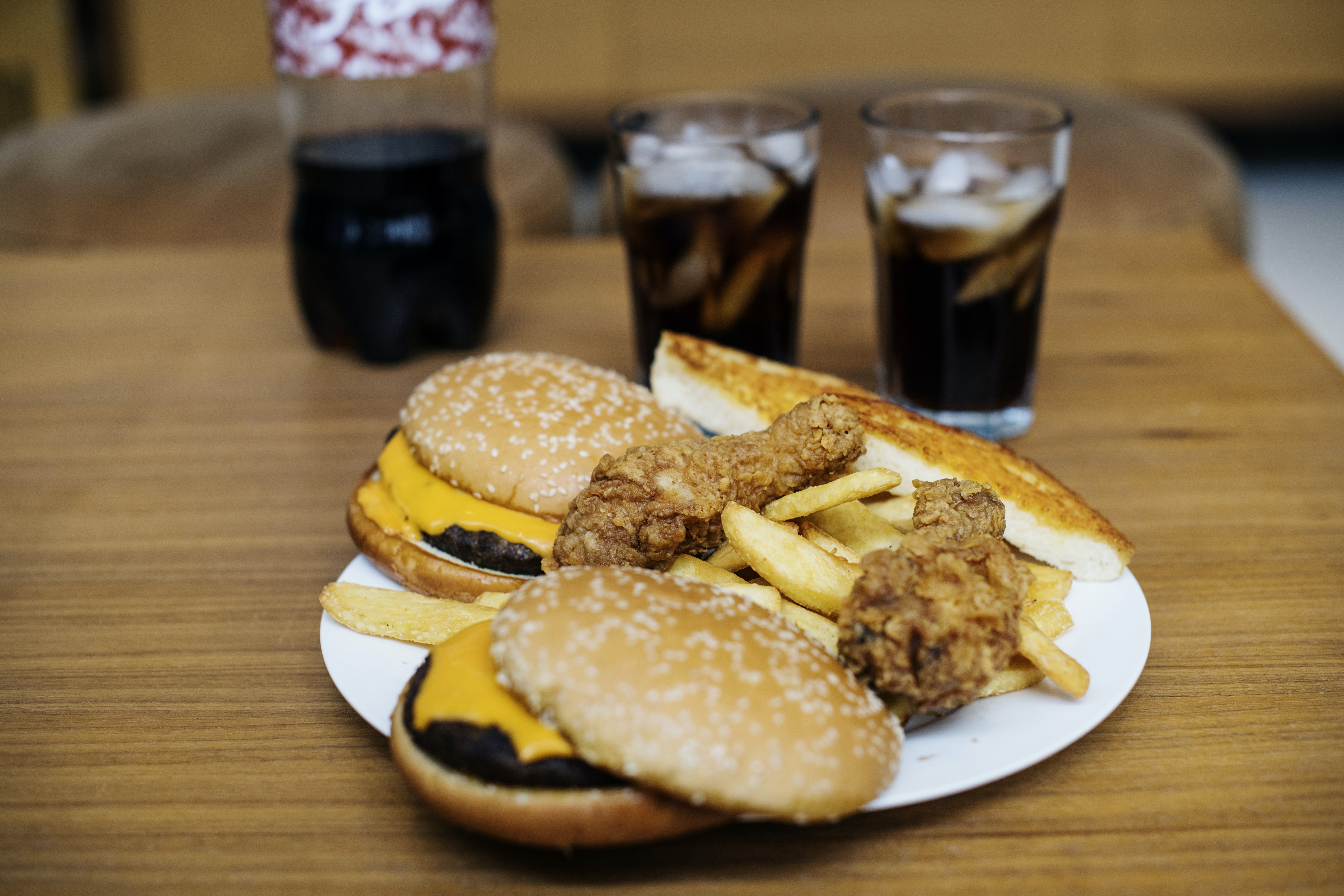 hamburger and chicken on white ceramic plate on brown wooden surface