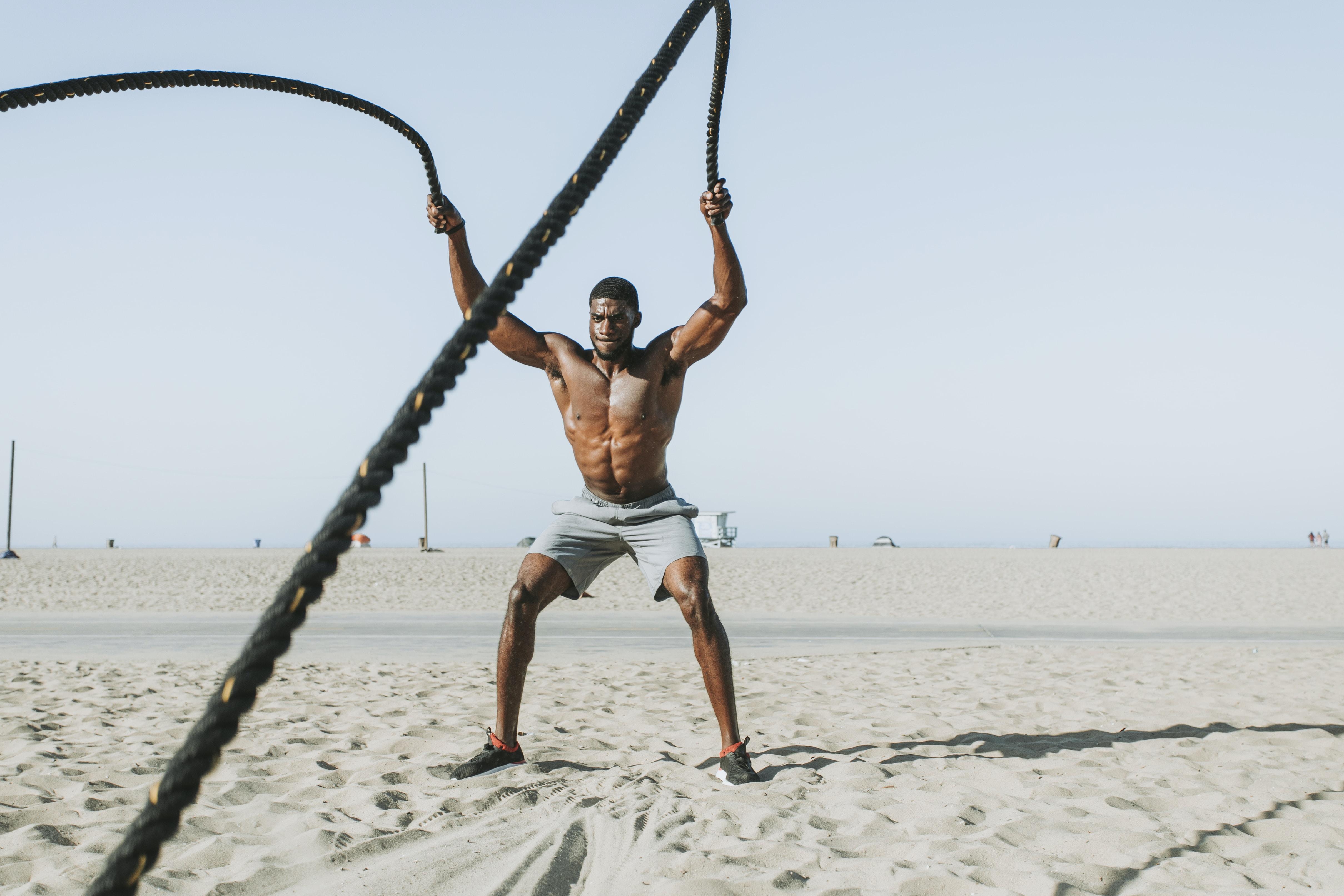man holding black ropes during daytime