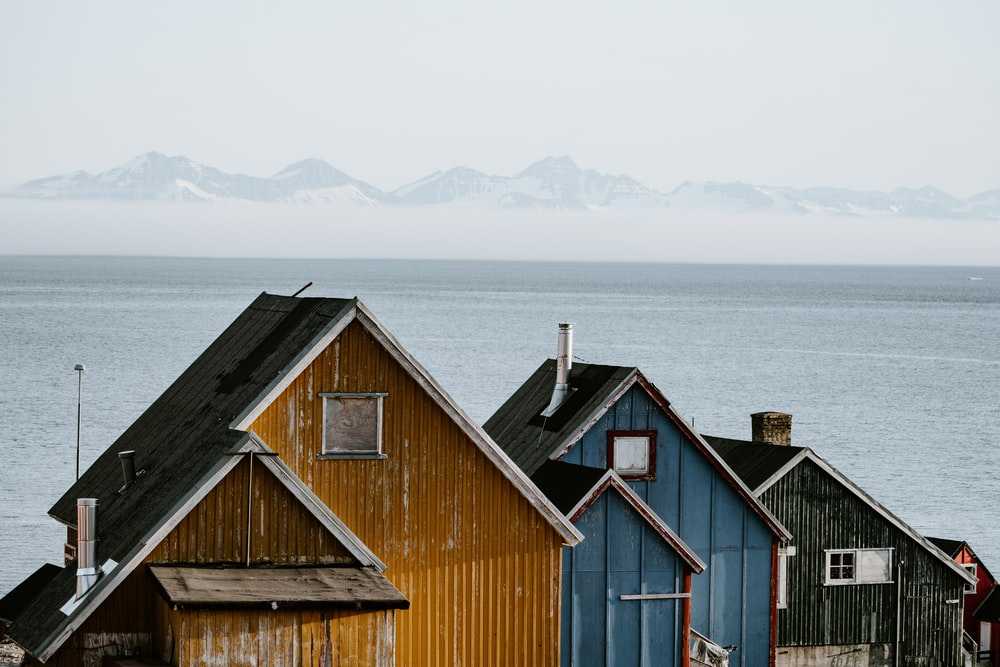 three orange, blue, and black wooden houses lined up in front of sea