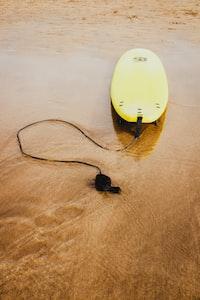 yellow bodyboard on shoreline