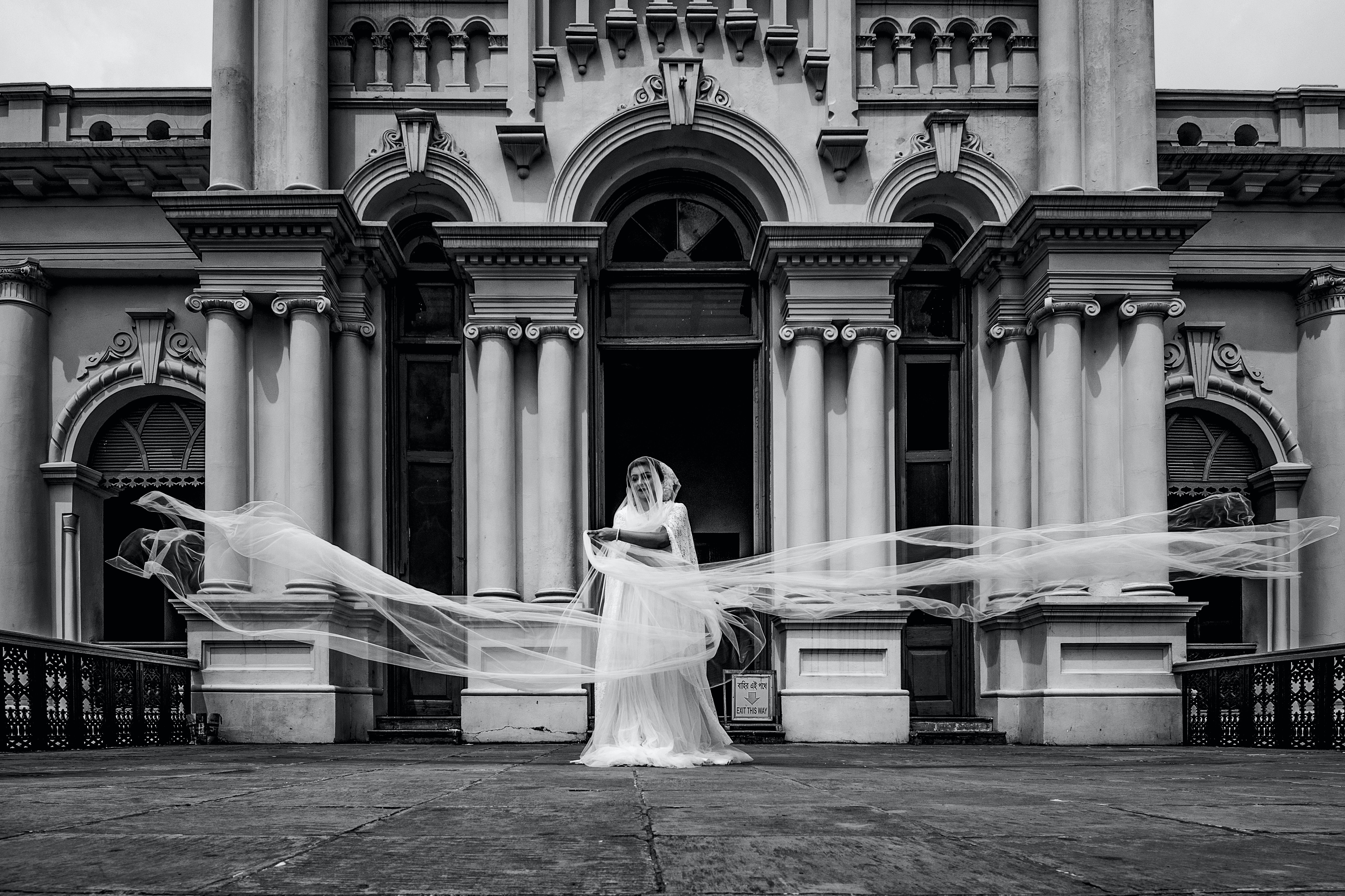 grayscale photography of bride beside concrete house