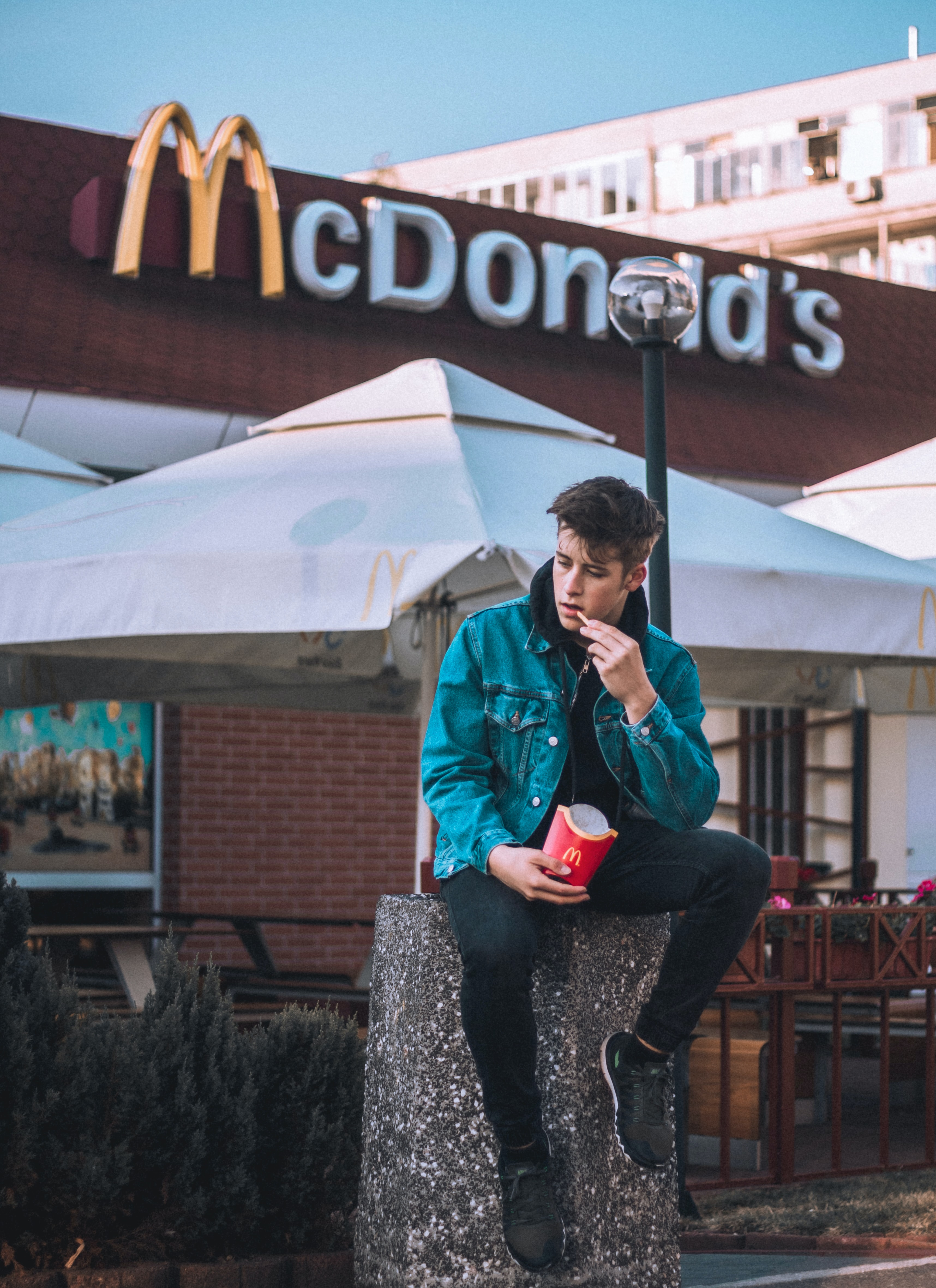 person sitting on pillar while eating fried fries outside McDonald's during