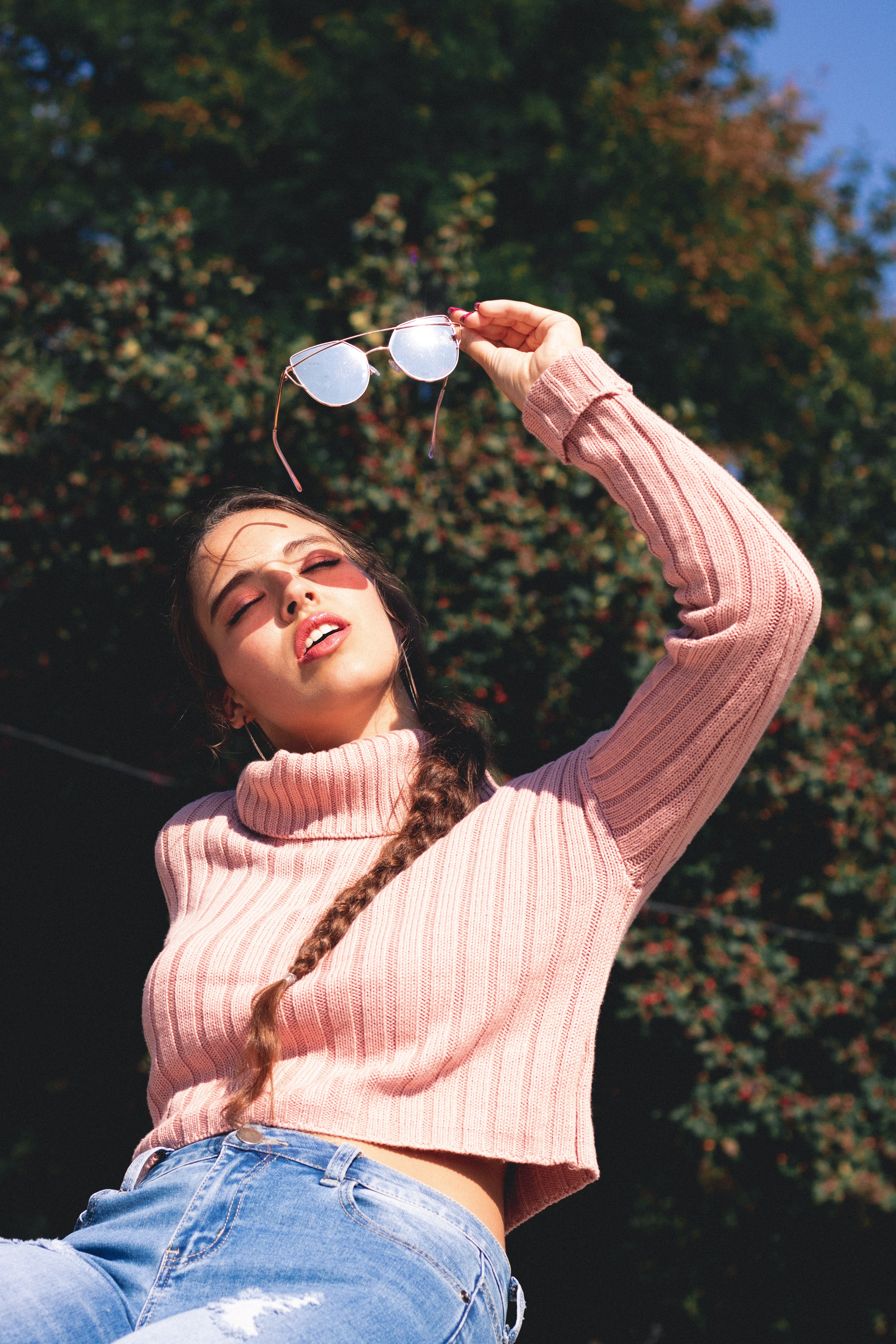 woman wearing pink sweater while holding sunglasses