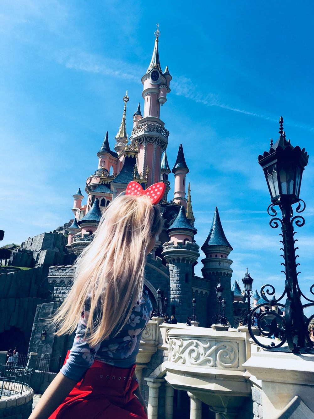 girl wearing red alice band looking at cinderella castle