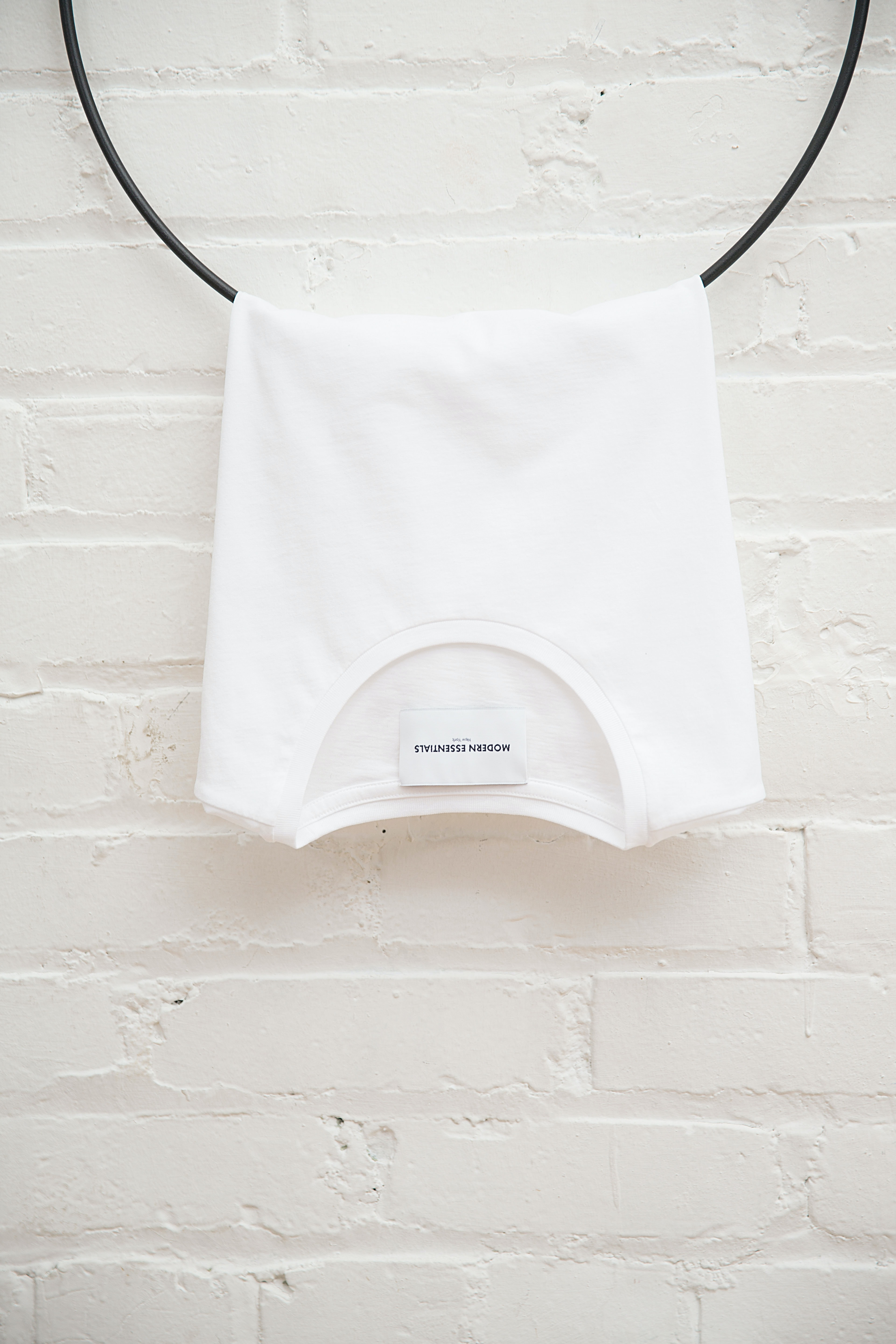 white crew-neck shirt hanging on black cable