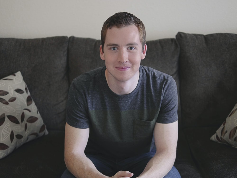 smiling man in gray shirt sitting on sofa