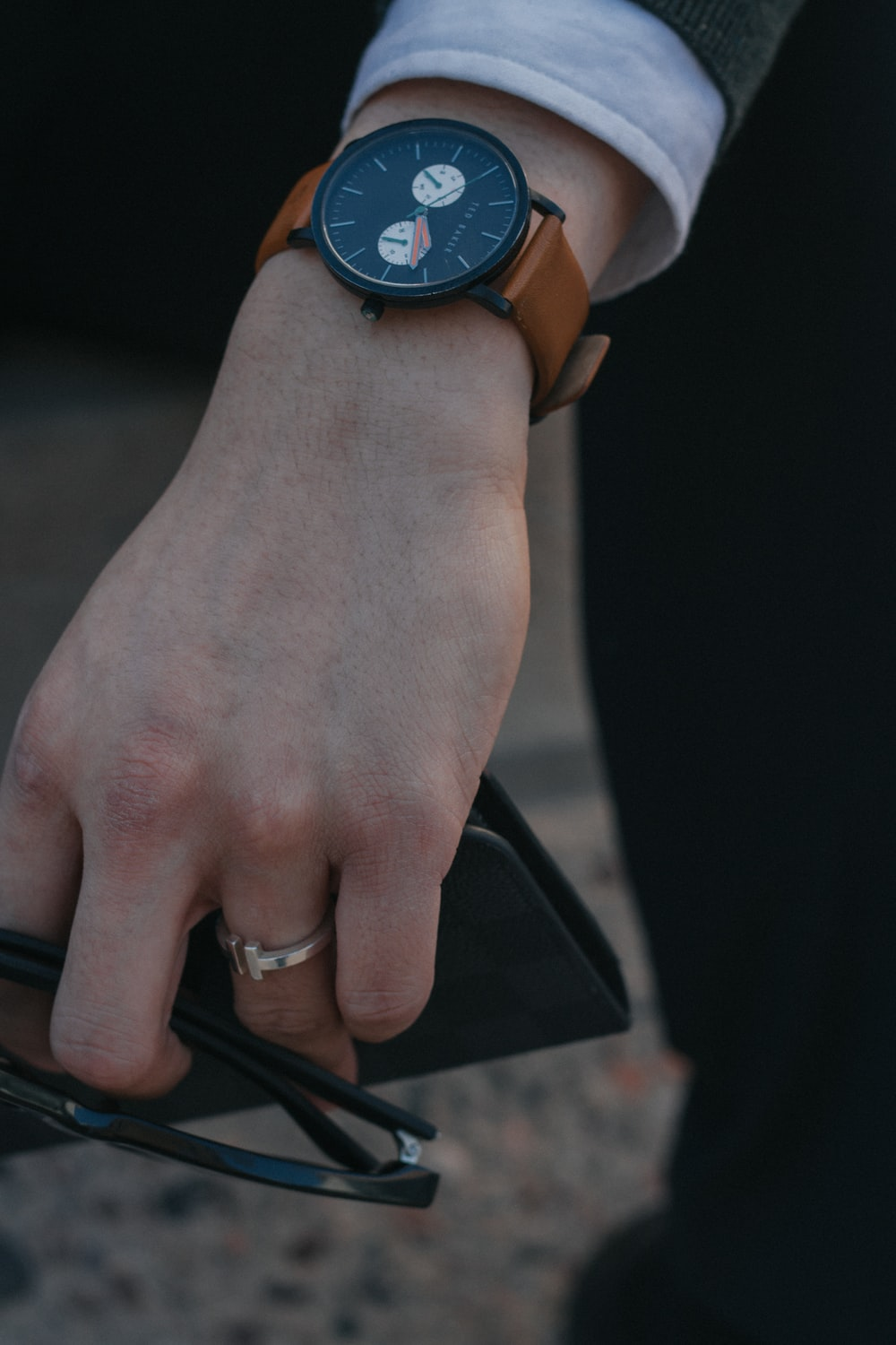 person holding sunglasses with black and brown watch