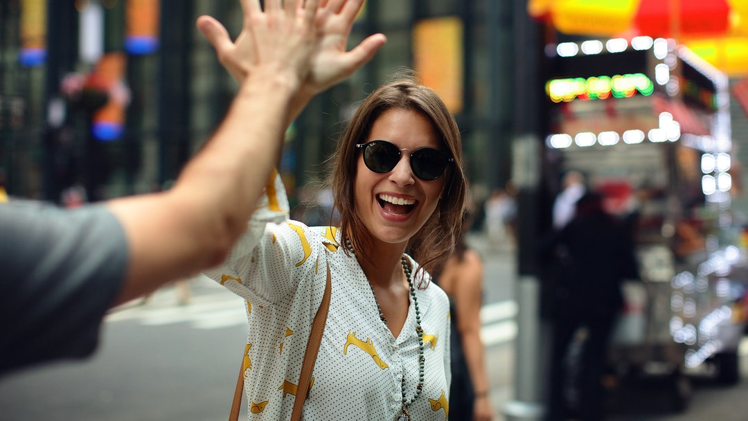 selective focus photography of smiling woman clapping on person hand