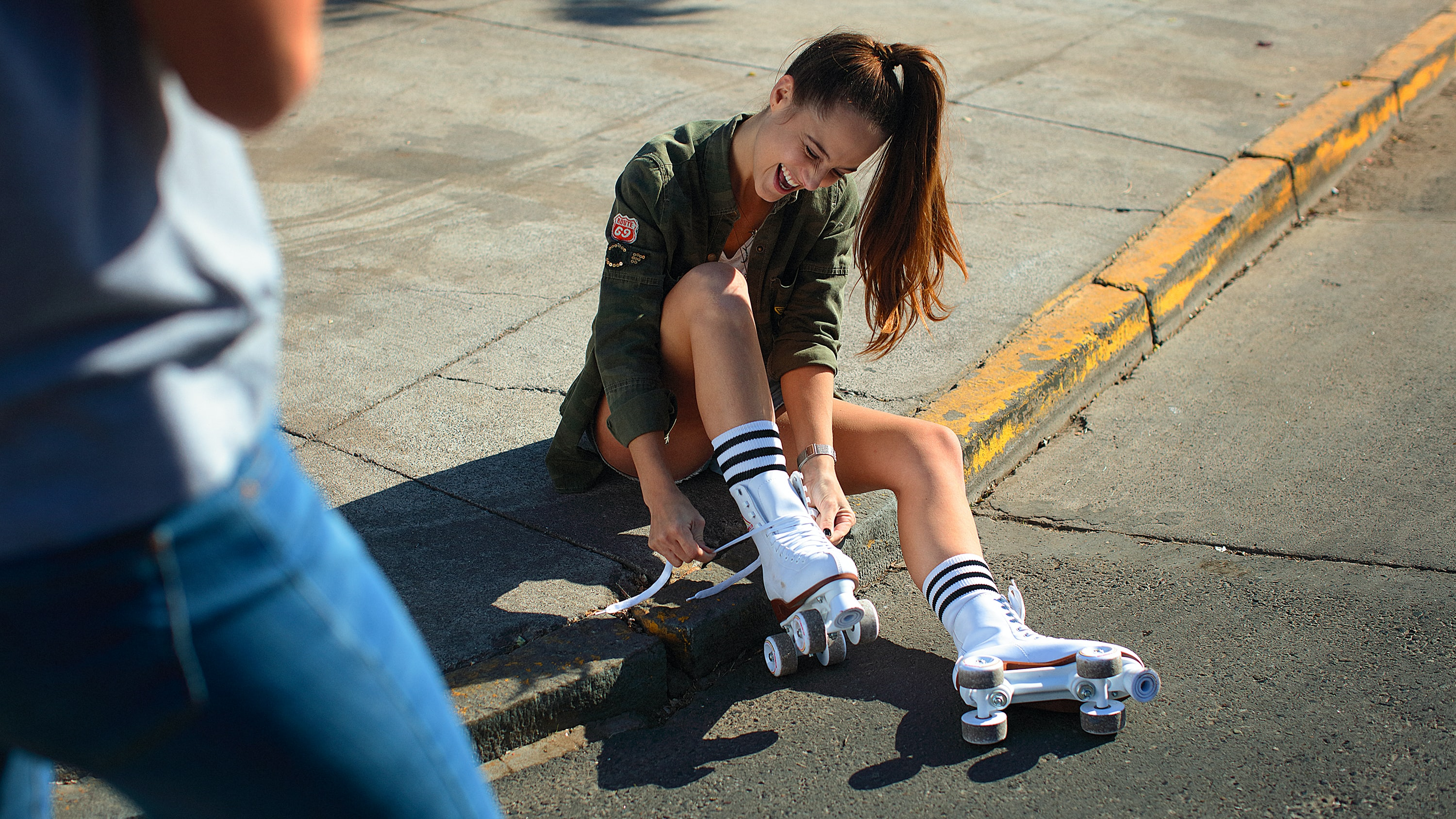 woman sitting on road shouldering while wearing pair of white roller blades at daytime