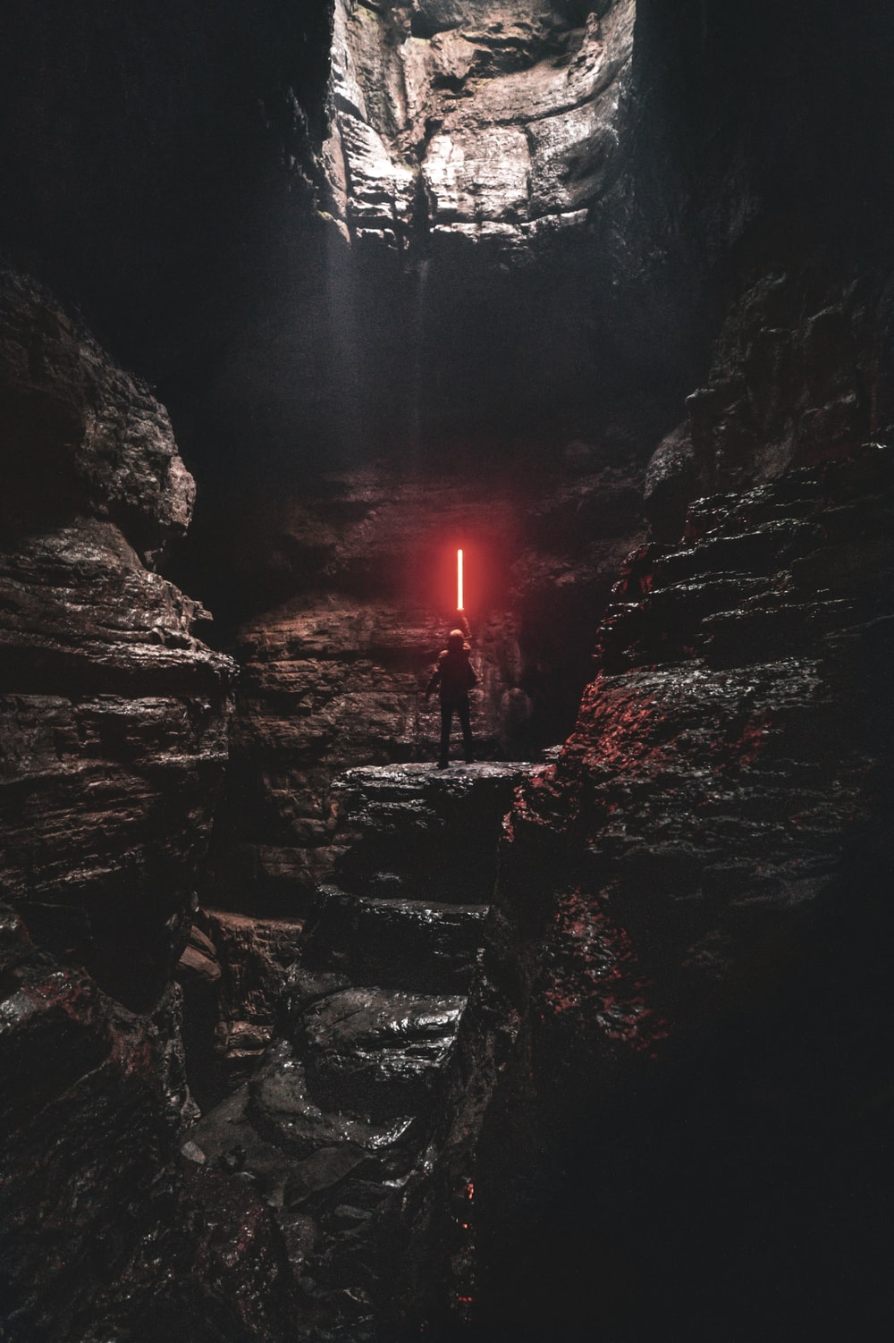 man holding red lightsaber standing on cliff