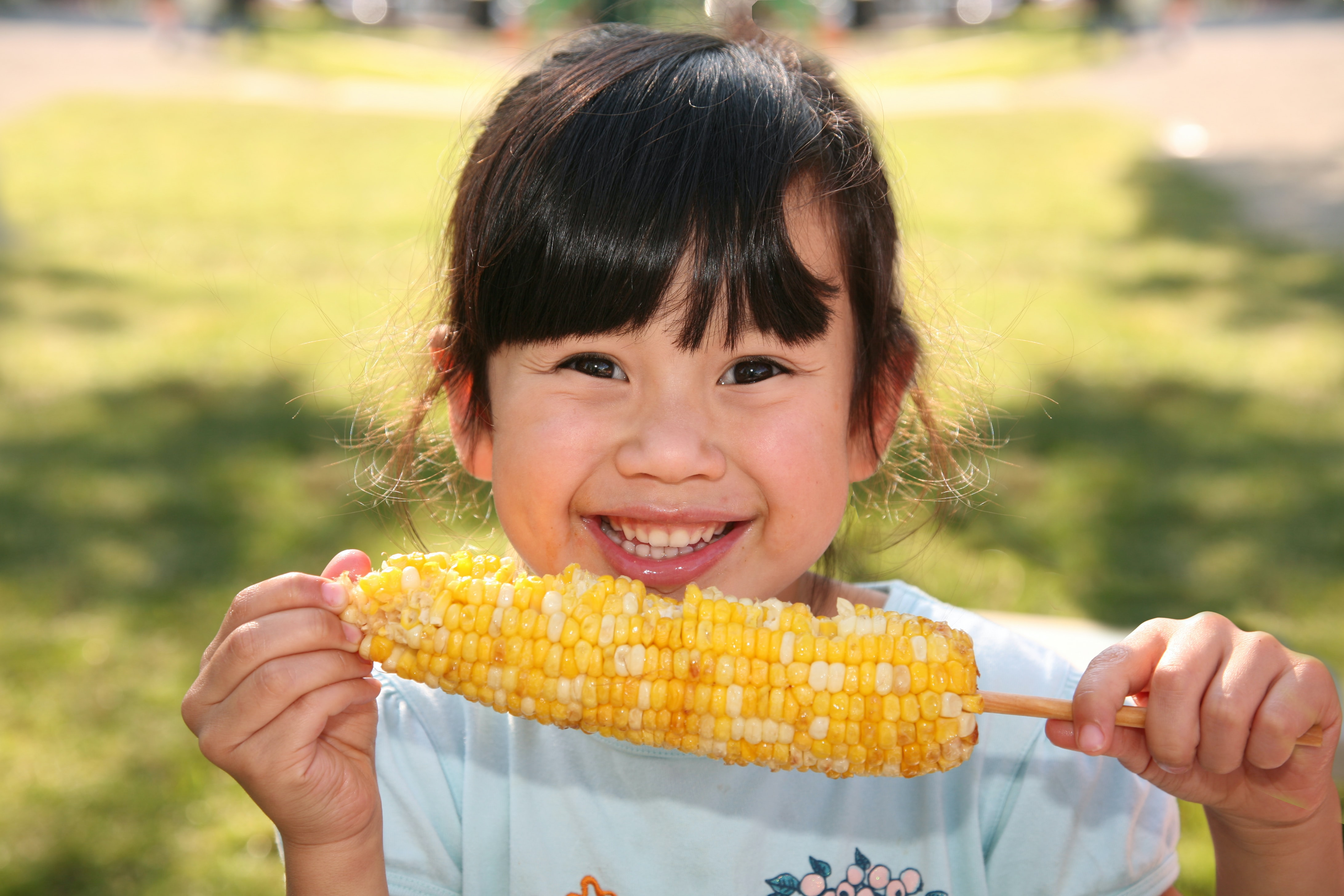 smiling girl holding cooked corn during daytime