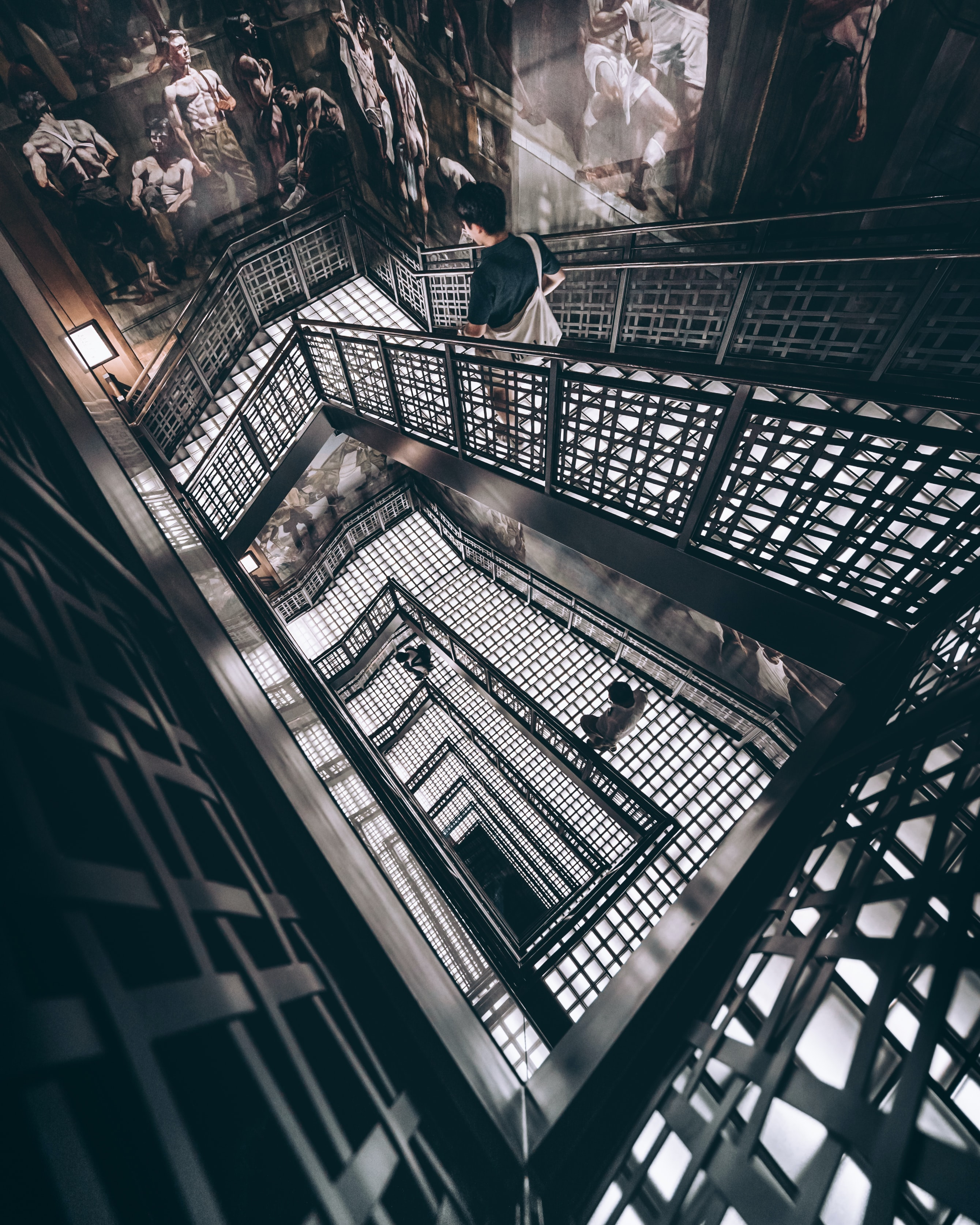 man walking on spiral staircase inside building