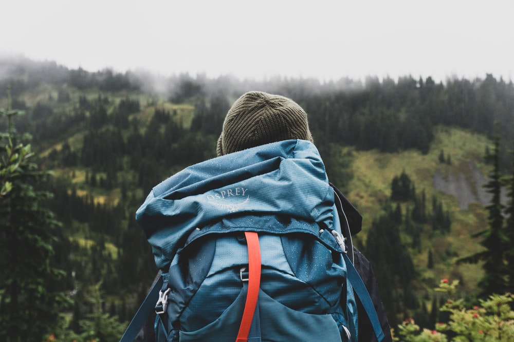person wearing teal backpack looking at mountain