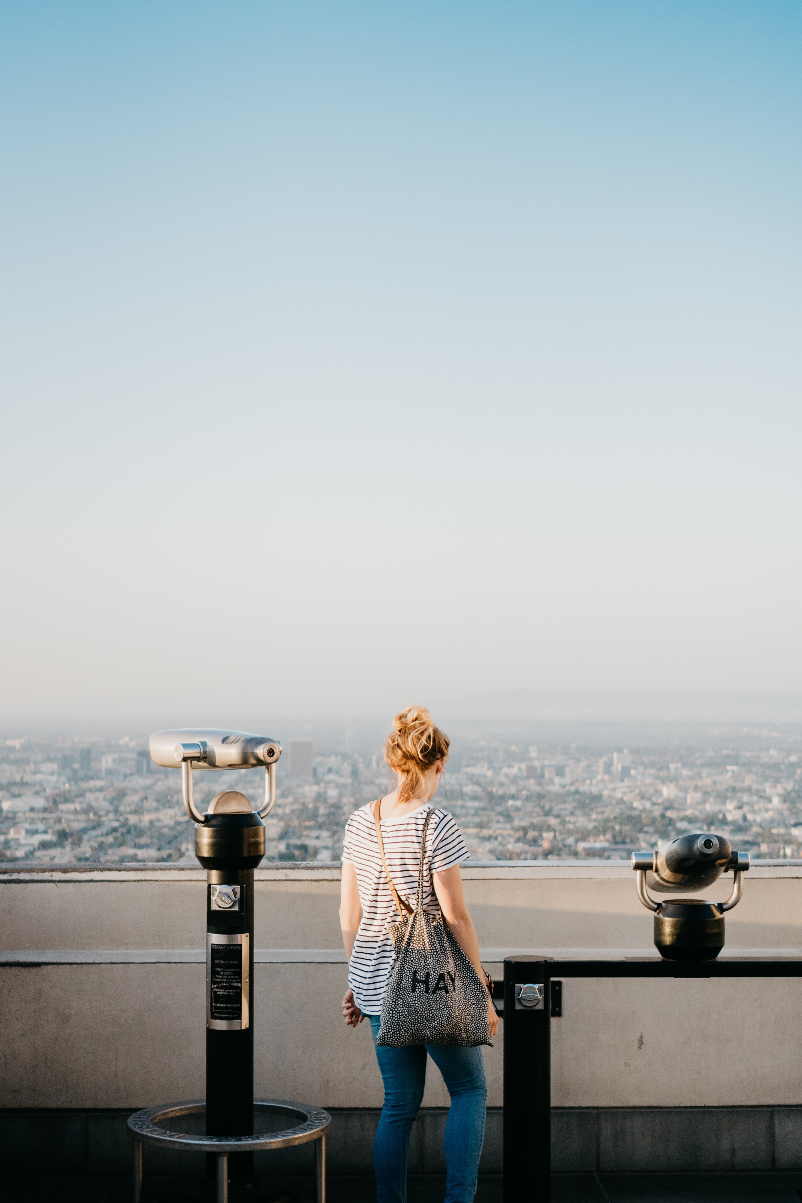 woman standing beside telescope during daytime