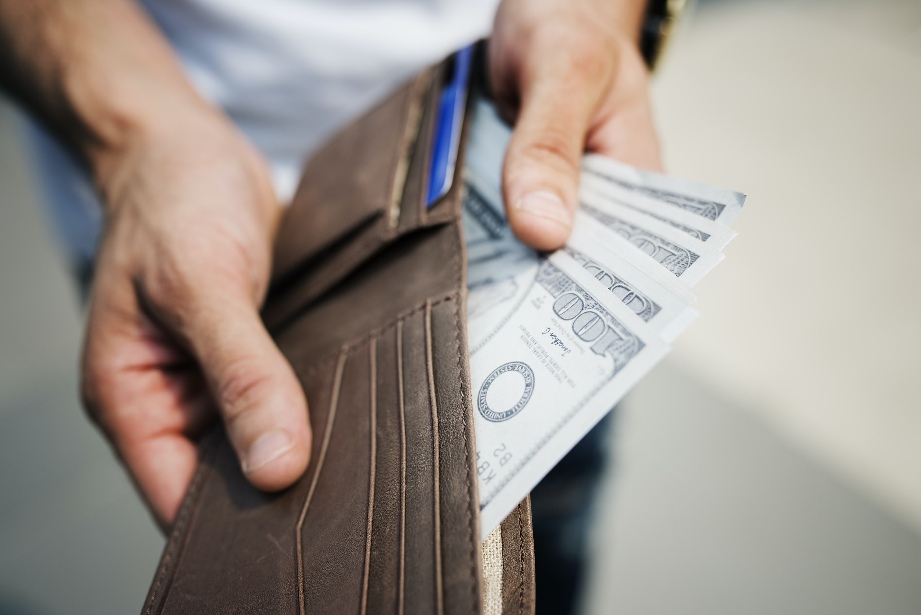 person showing brown leather wallet with banknotes