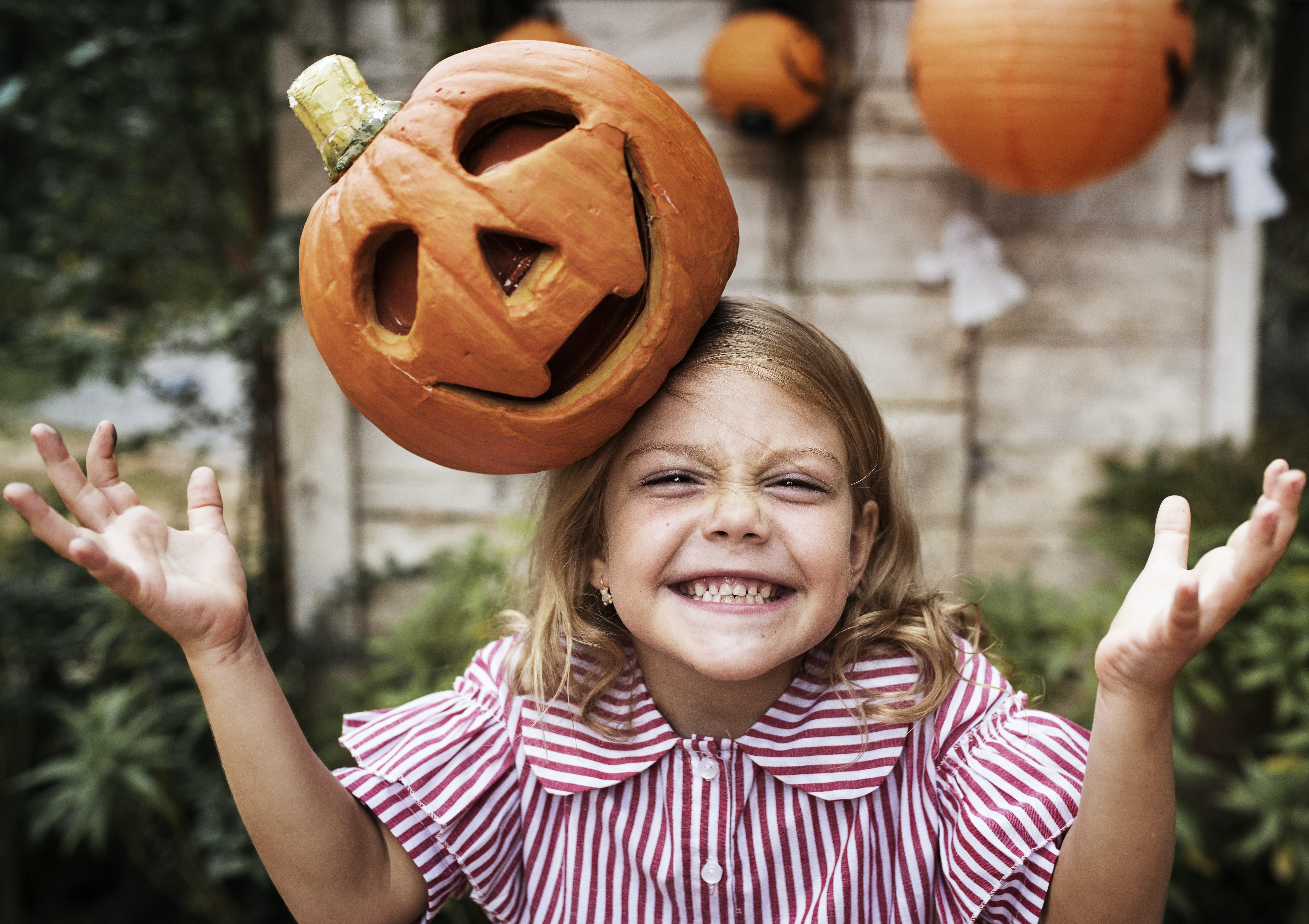 smiling girl with Jack O'Lantern on her head