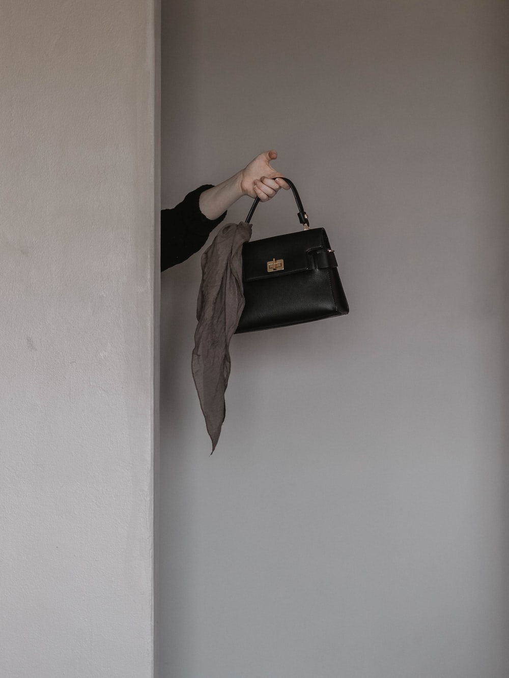 person holding black leather handbag