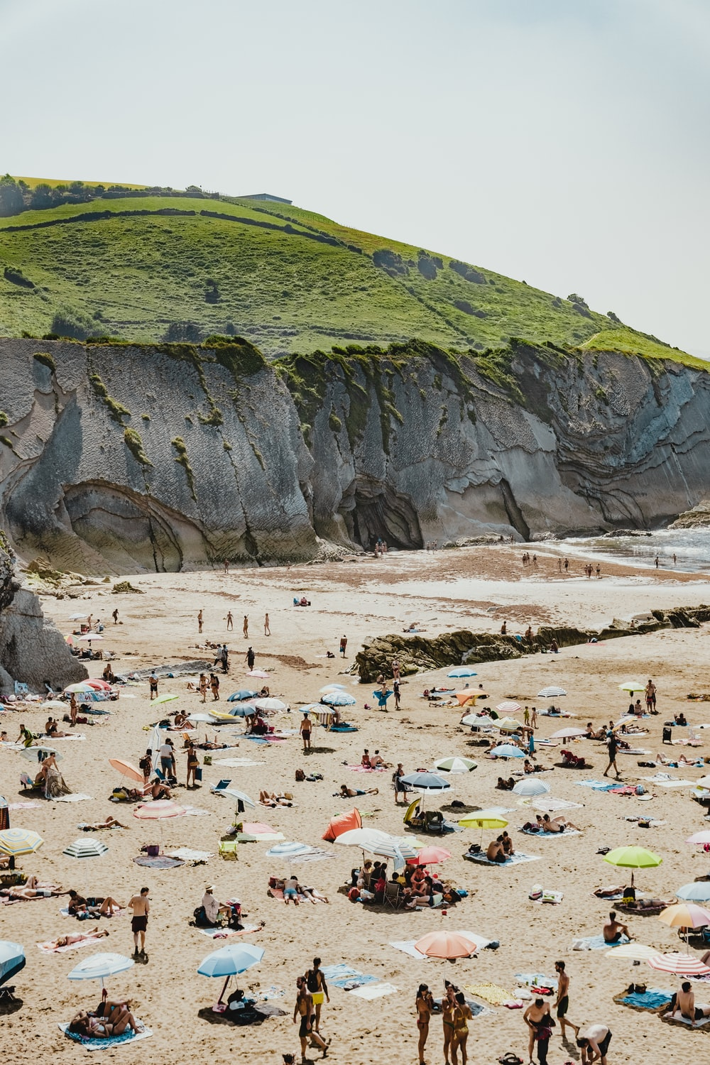 people on beach beside hill during daytime