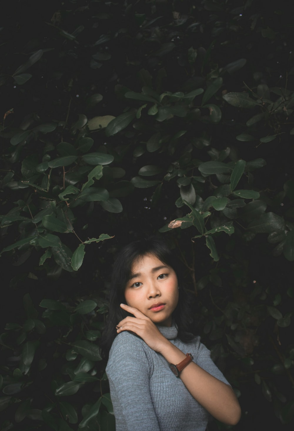 girl wearing gray turtle-neck top standing beside green tree posing for photo