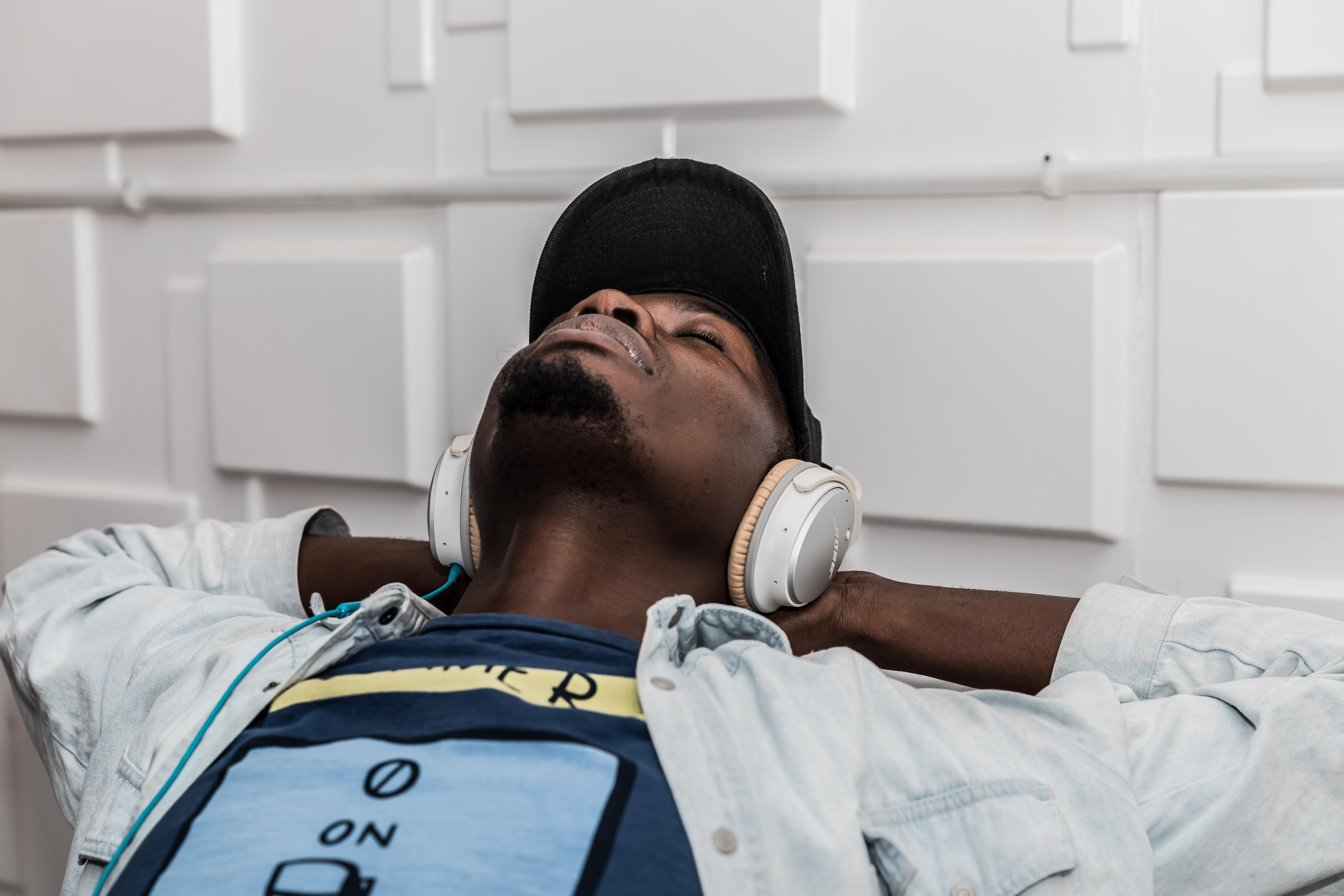 man wearing denim jacket wearing headphones and listening to music