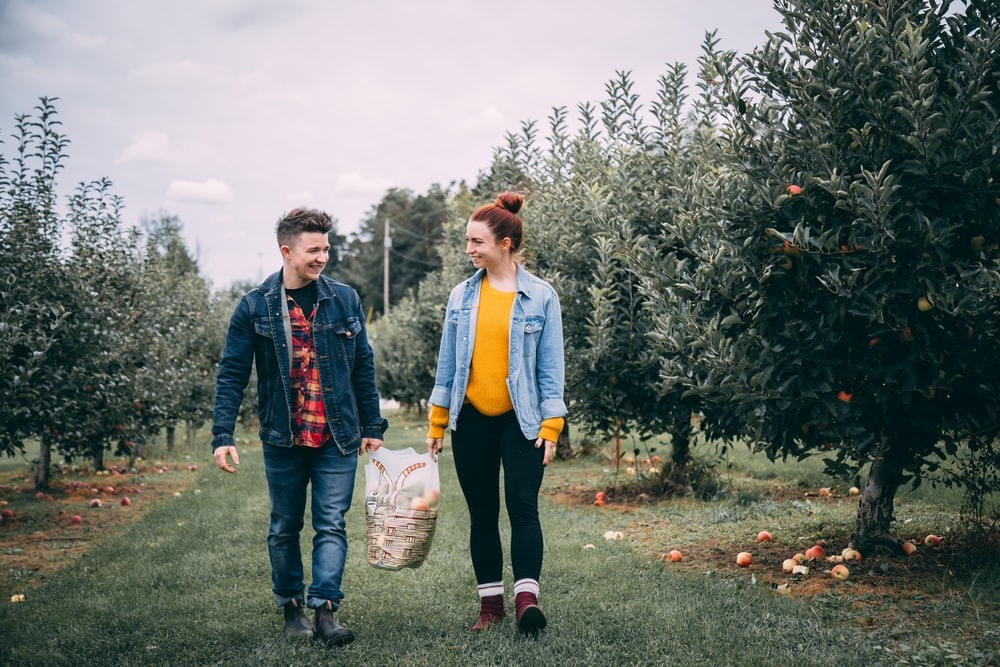 man carrying bag with woman in fruit tree orchard at daytime