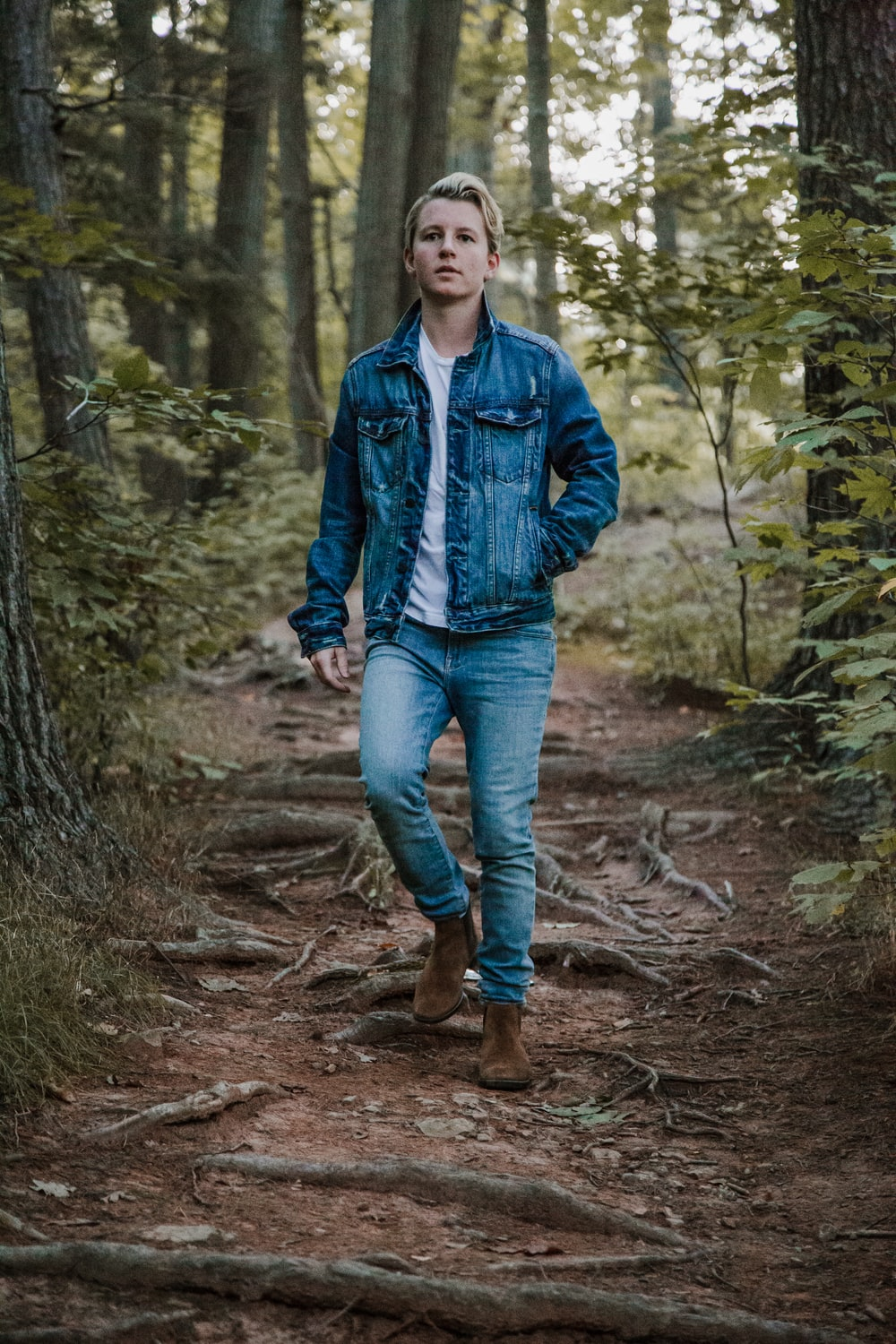 men's blue denim button-up jacket between trees
