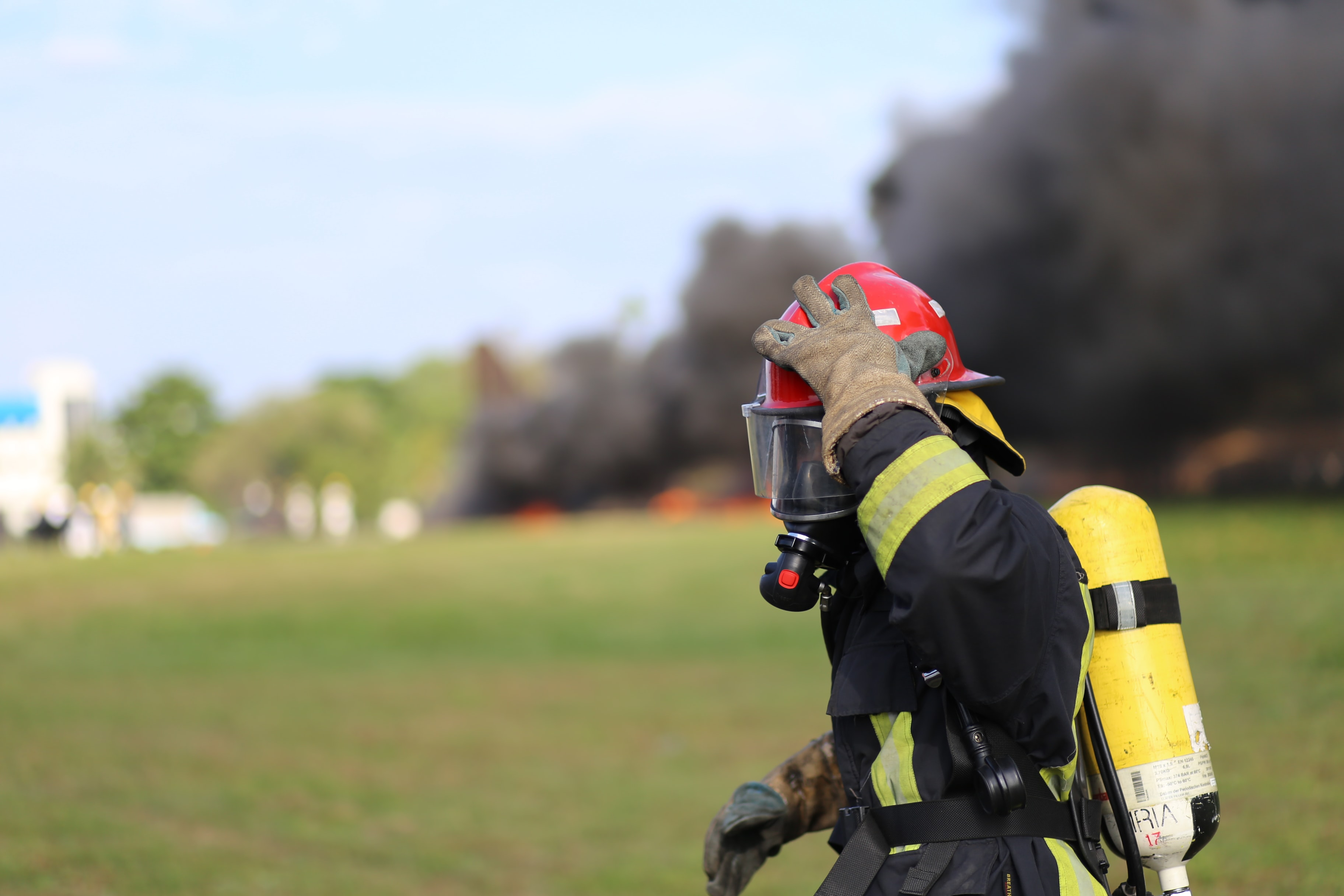 firefighter touching own helmet during day