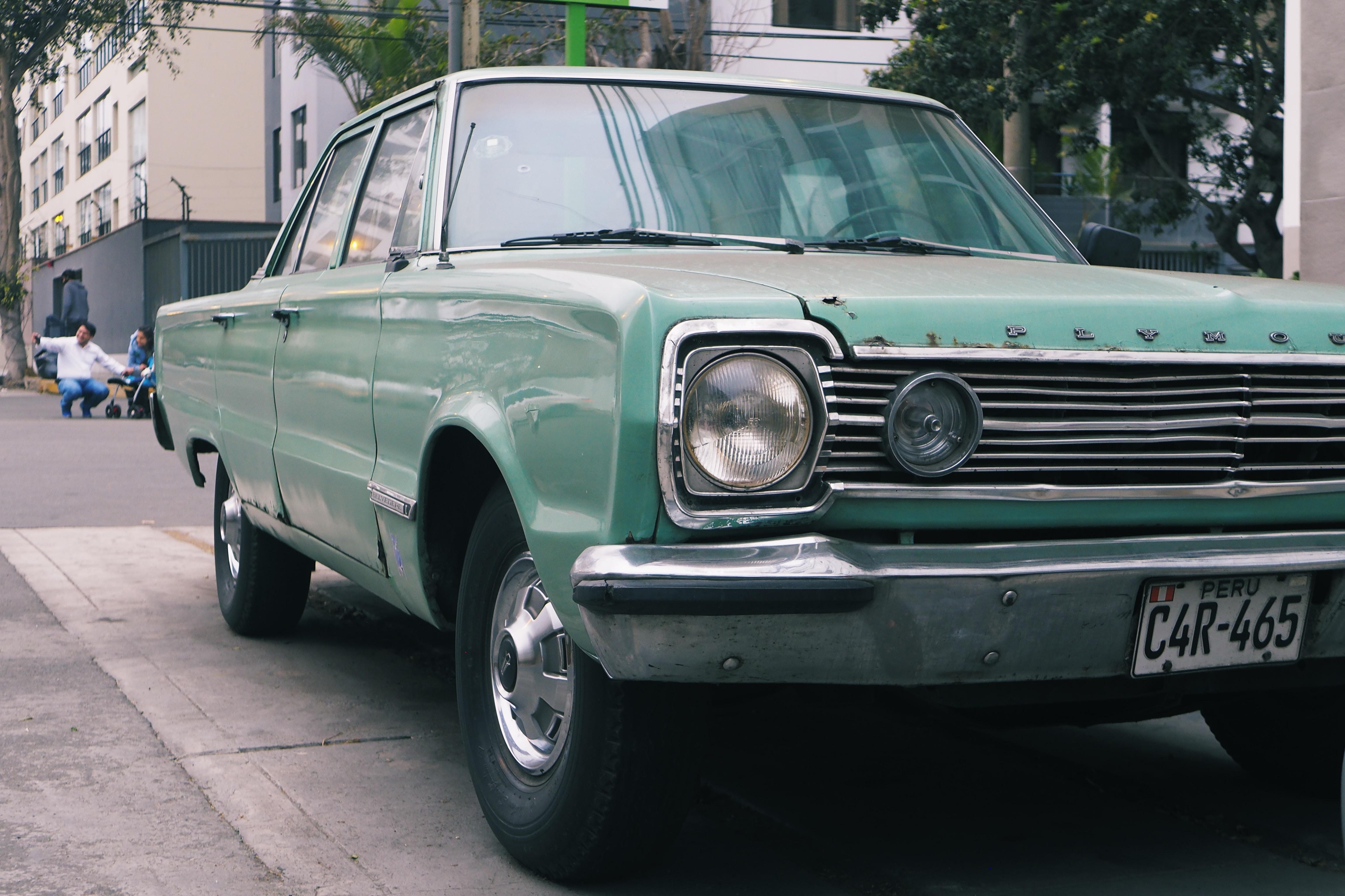 closeup photo of green sedan parked beside tree taken at daytime