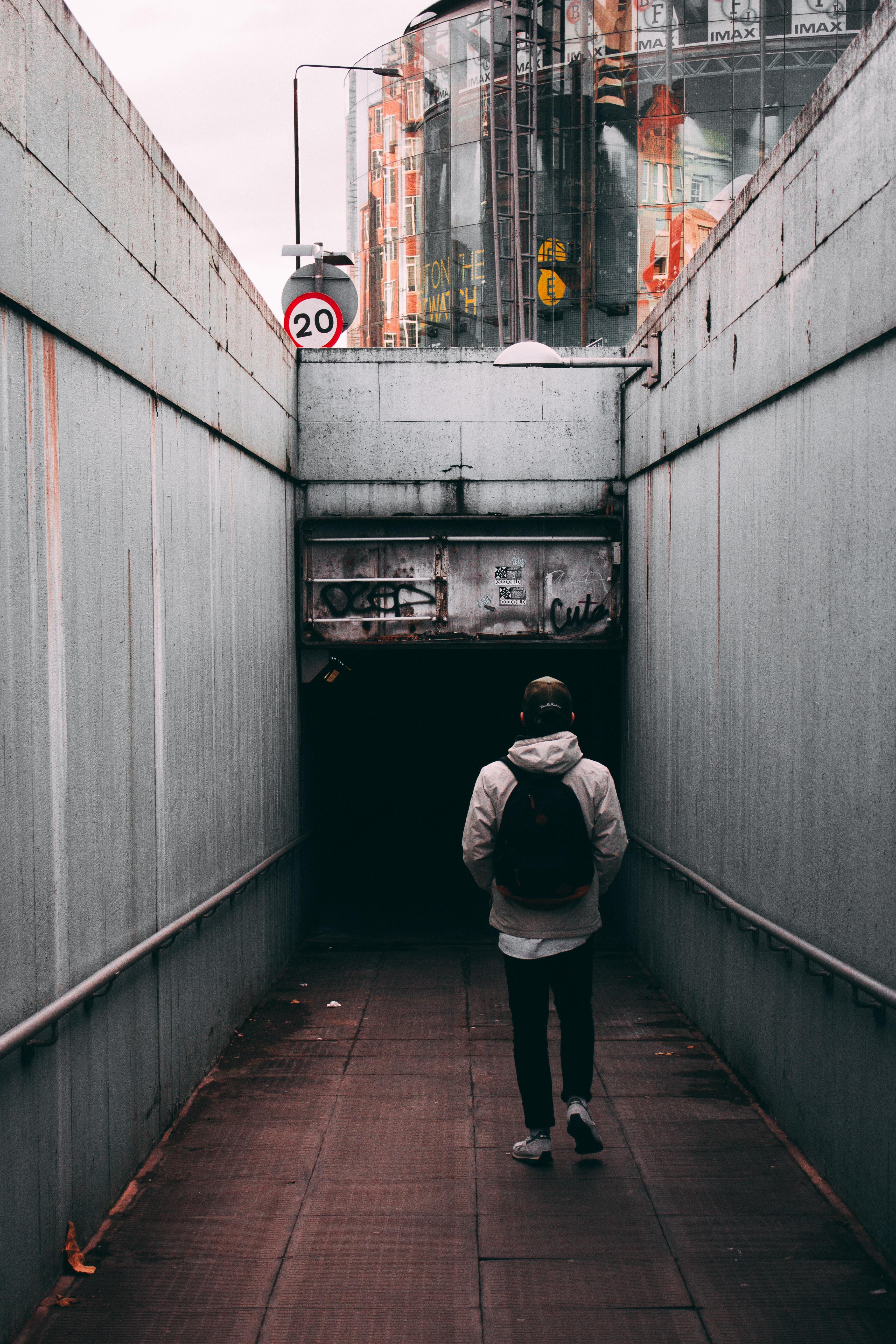 person walking near gray walls