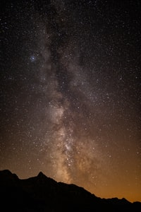 silhouette of mountain and stars during night time