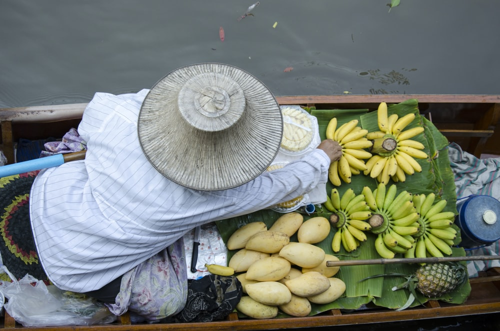 person in boat floating on body of water with fruits