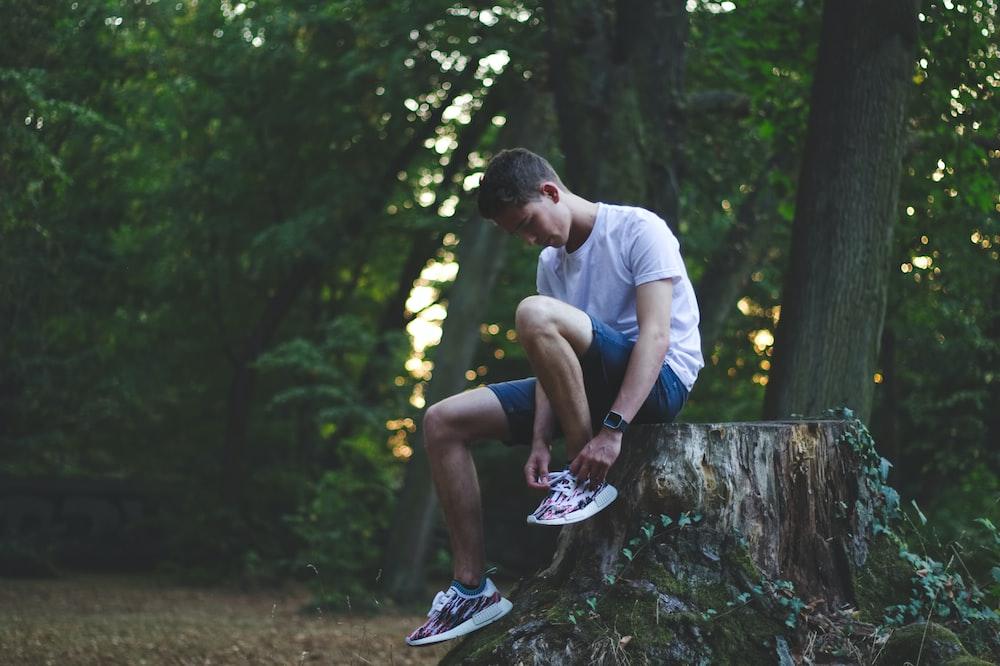 man sitting while holding shoe near trees