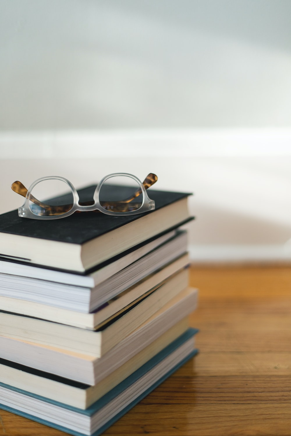 clear framed eyeglasses on top of pile of books
