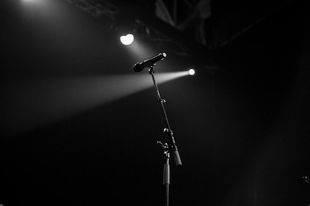 greyscale photo of microphone near spotlight