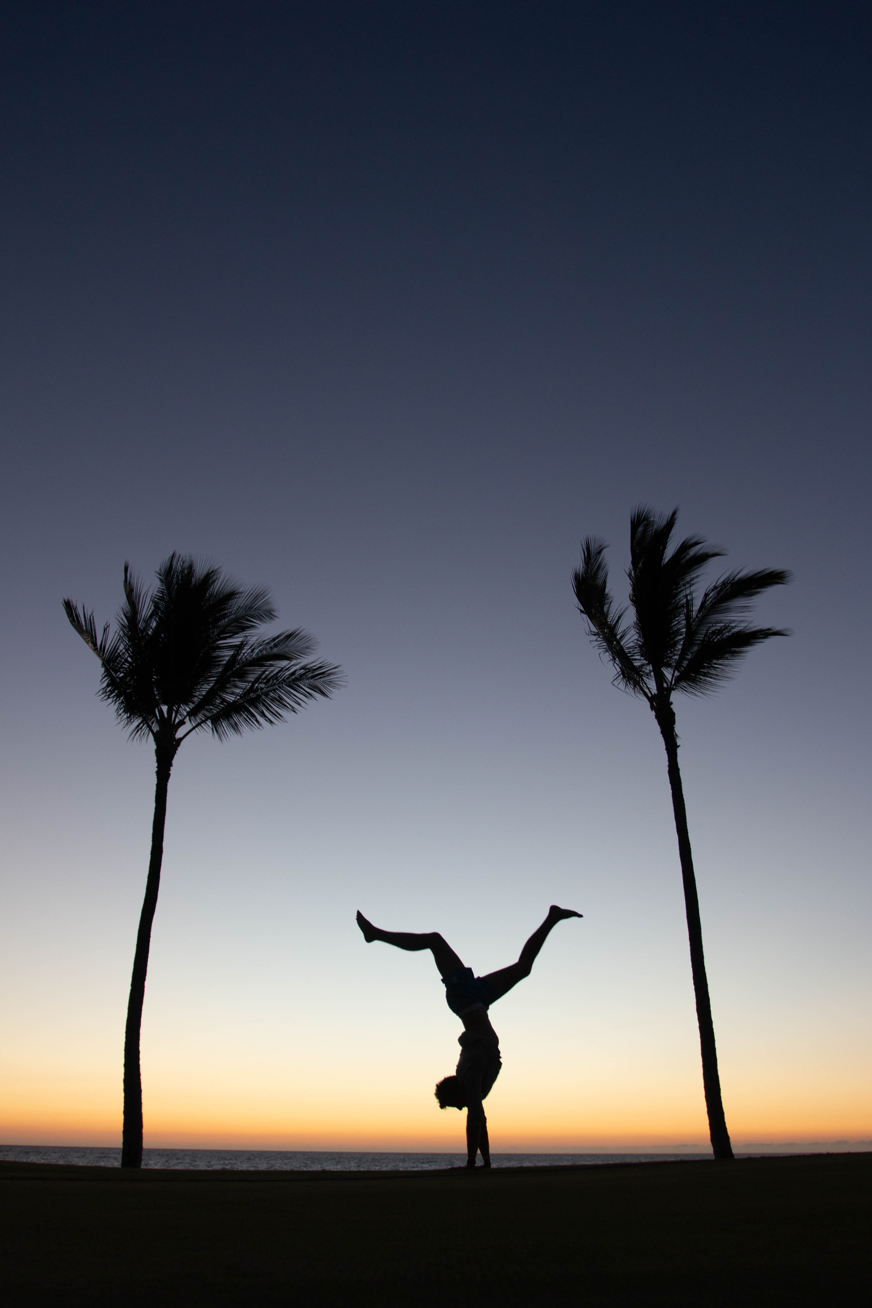 man doing exercise during sunset