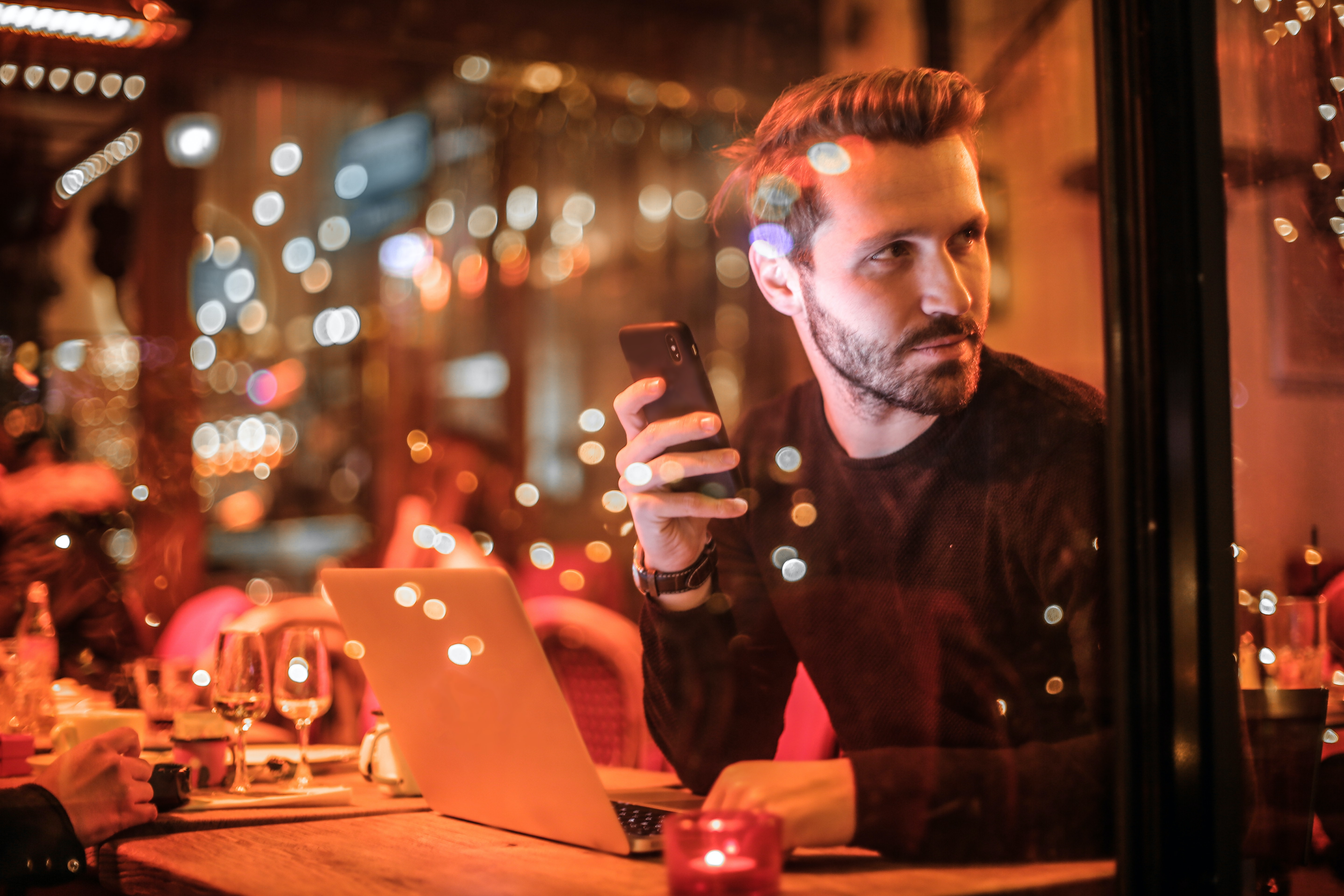 man holding smartphone beside table