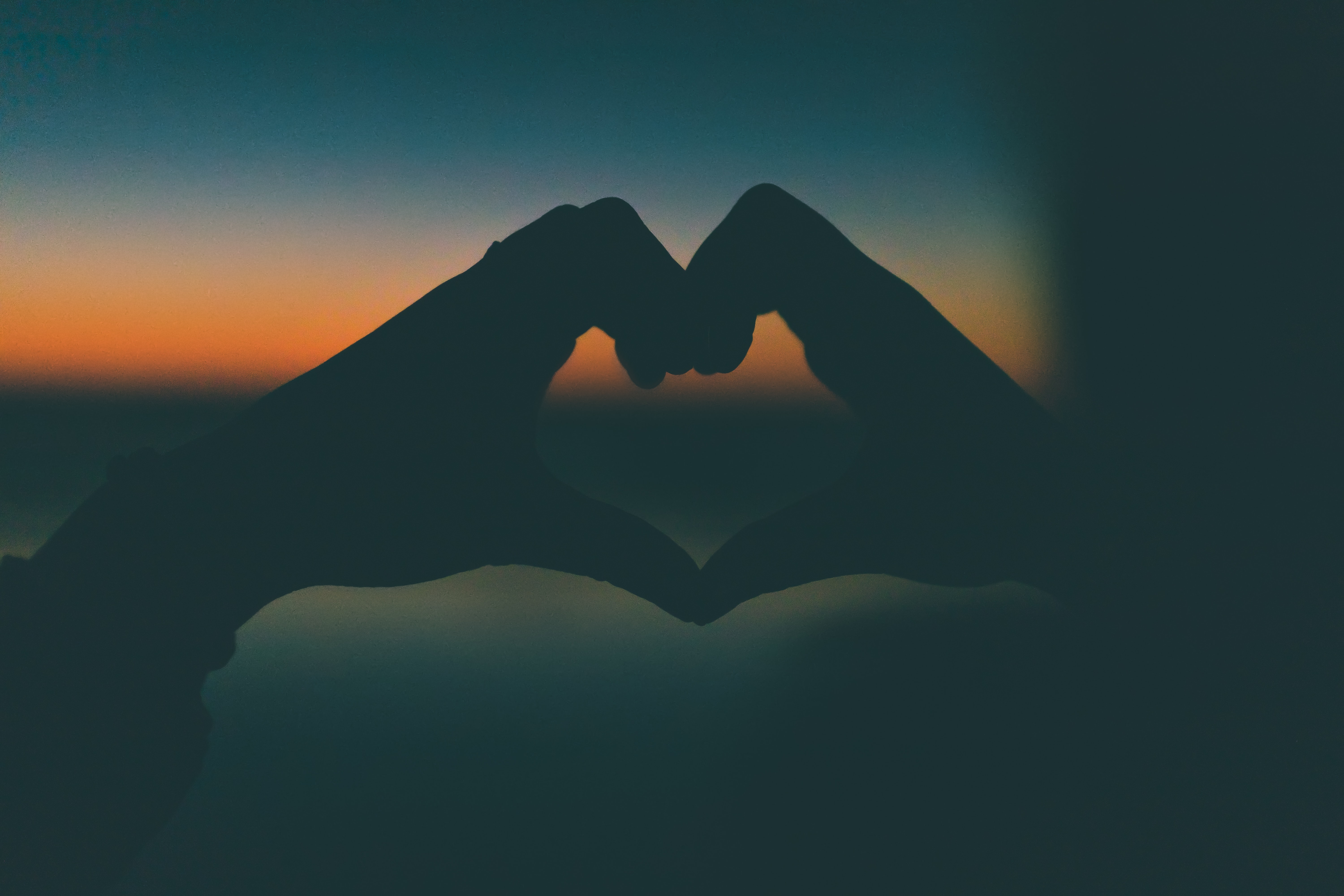 silhouette photography of heart form hands