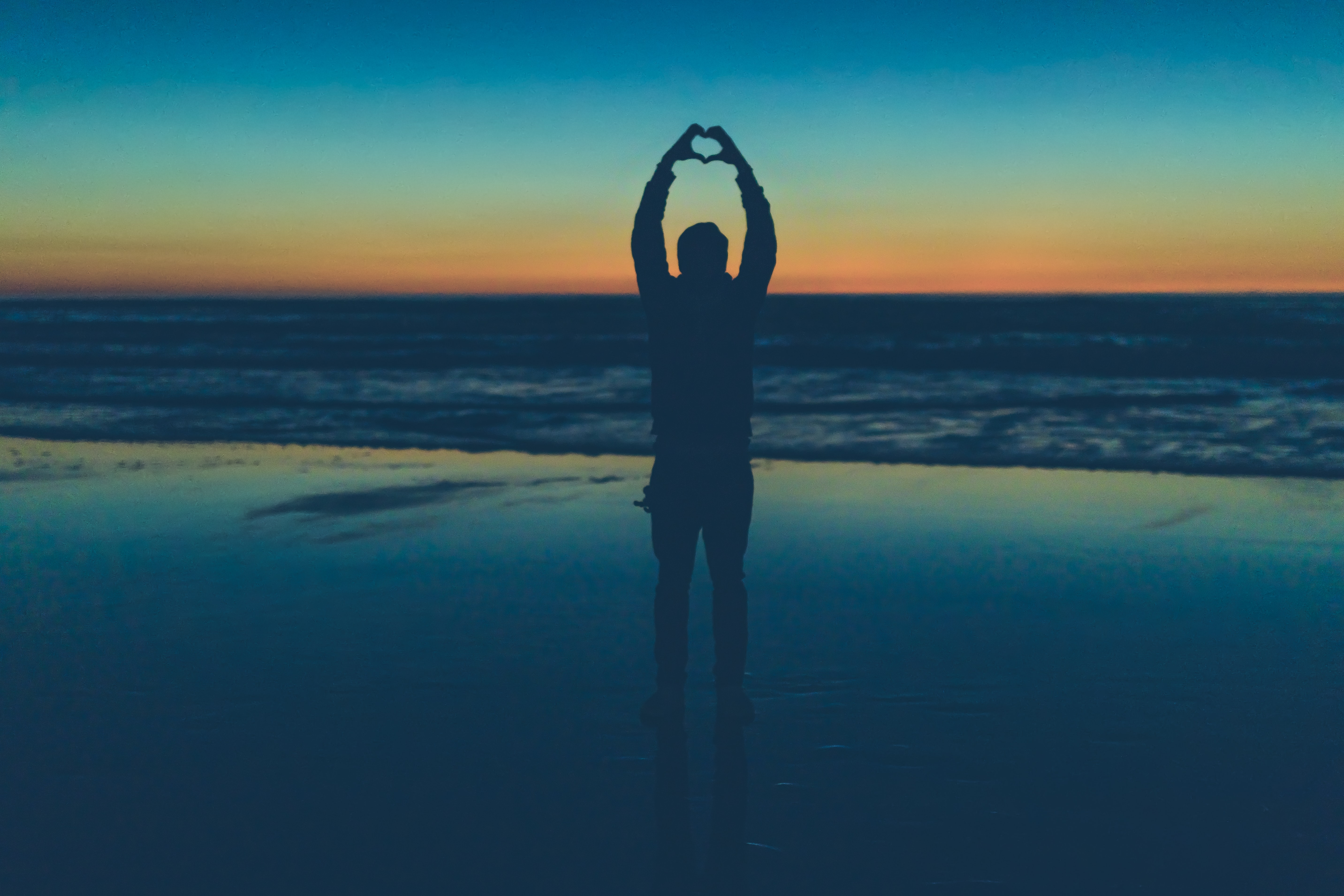 silhouette of person making heart sign near seashore