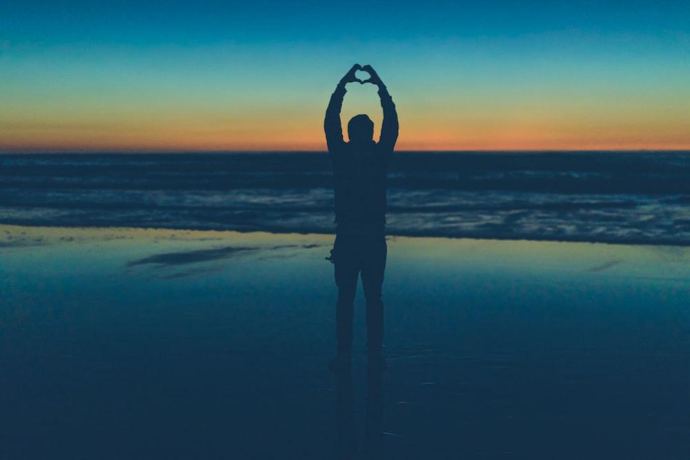 silhouette of person making heart sign near seashore